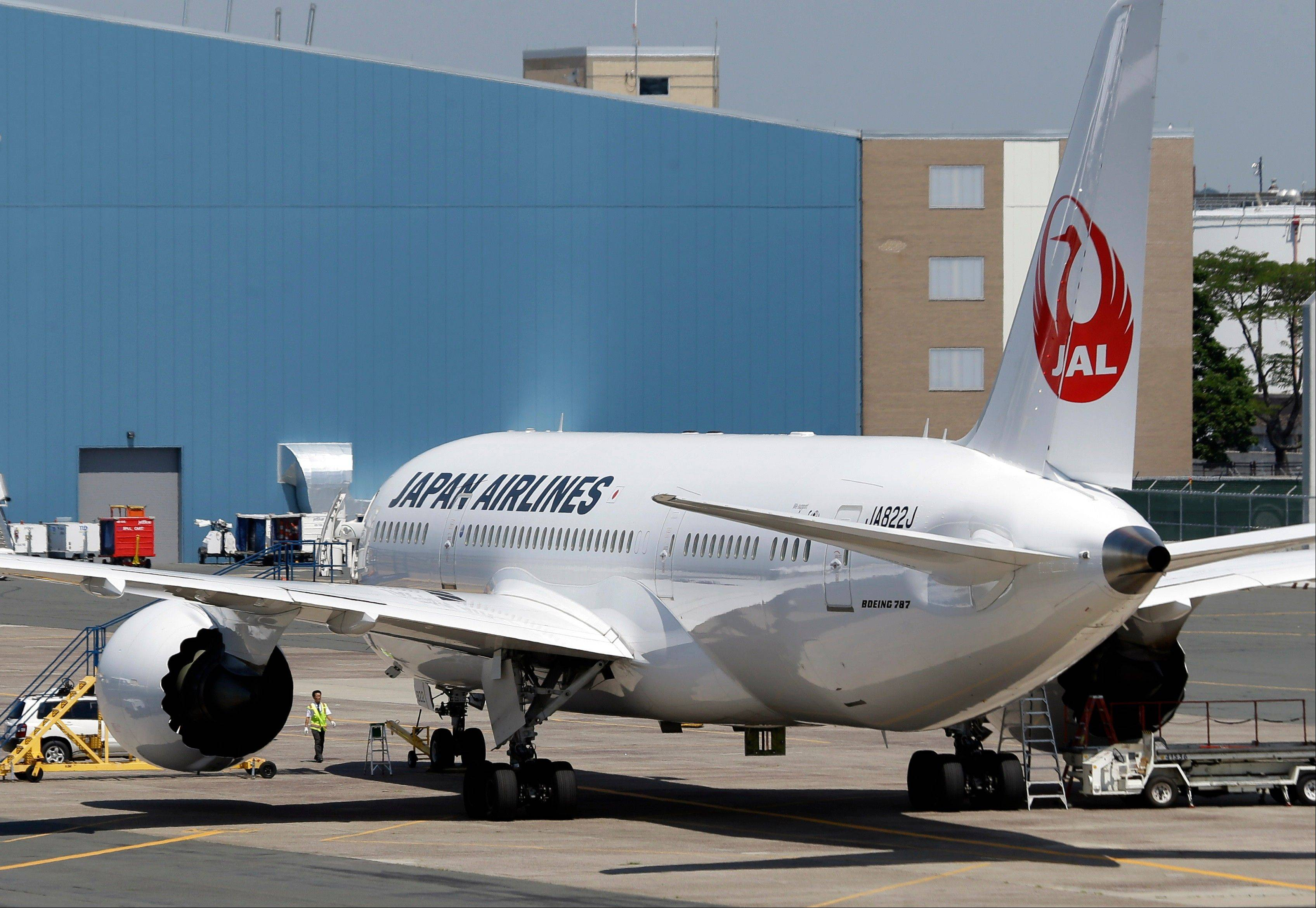 An airport worker approaches a Japan Airlines Boeing 787 aircraft as it sits on the tarmac Friday at Terminal E at Logan International Airport in Boston. The JAL aircraft's flight to Tokyo returned to Boston on Thursday because of a possible fuel pump issue. It's the latest trouble for the new Dreamliner aircraft.