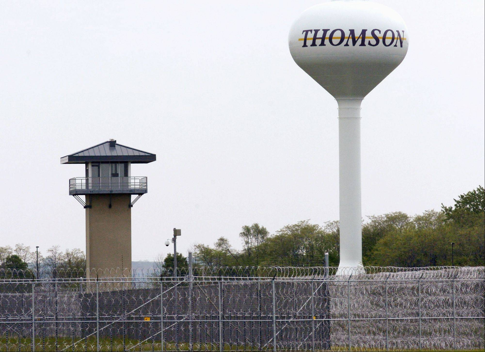 A guard tower overlooking a fence and coils of wire surrounding the Thomson Correctional Center in Thomson, Ill.