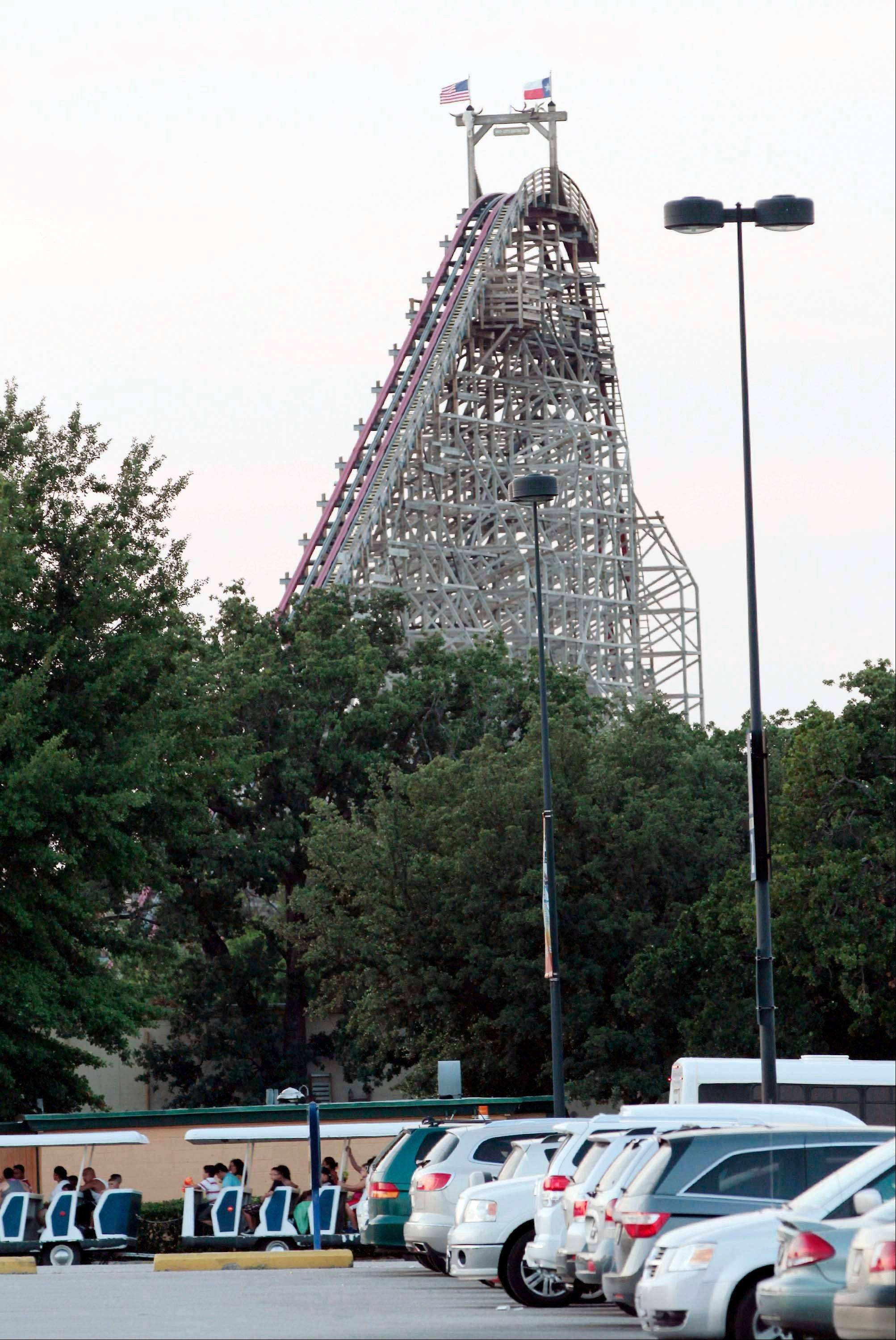 Patrons leave Six Flags Over Texas park Friday. The Texas Giant roller coaster was shut down after an adult woman fell to her death, witnesses say.