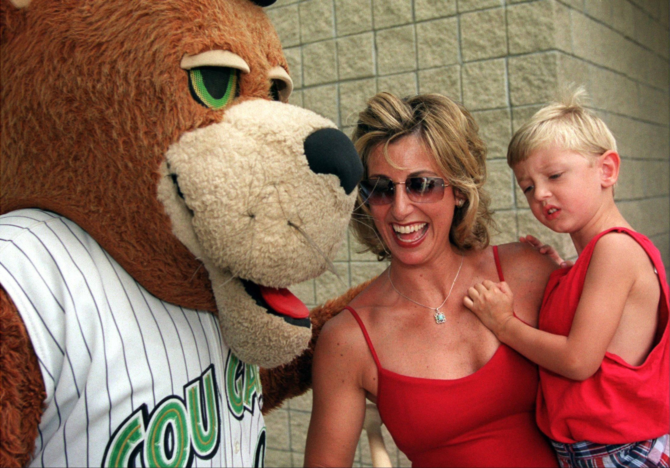 Jill Card of Winfield is congratulated by Ozzie, the Kane County Cougars mascot, after being told in August 2002 she was the 5 millionth fan through the gate at what was then Elfstrom Stadium in Geneva. Her son E.J., 4, seems unmoved.