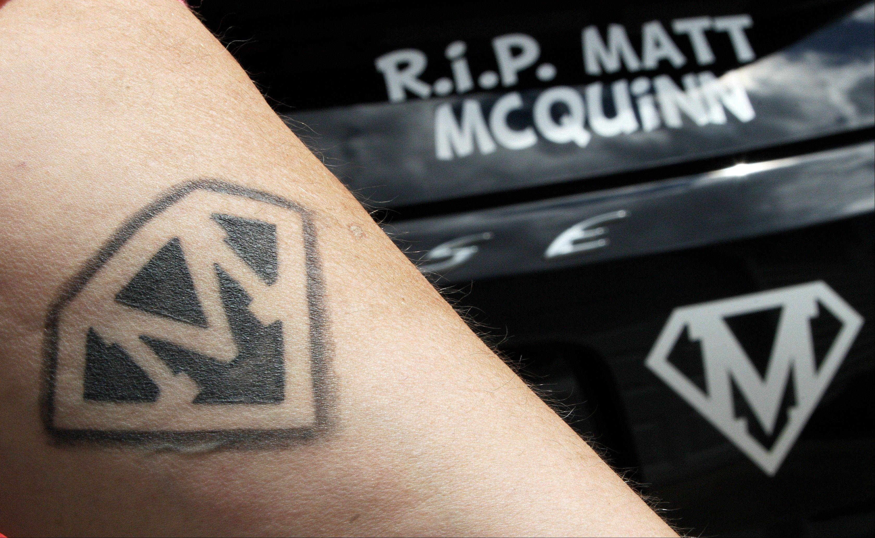 Jerri Jackson, mother of Aurora, Colo. theater shooting victim Matthew McQuinn, shows her tattoo of his initials as she stands next to her car with decals in memory of her son in Springfield, Ohio on Sunday, July 14, 2013.