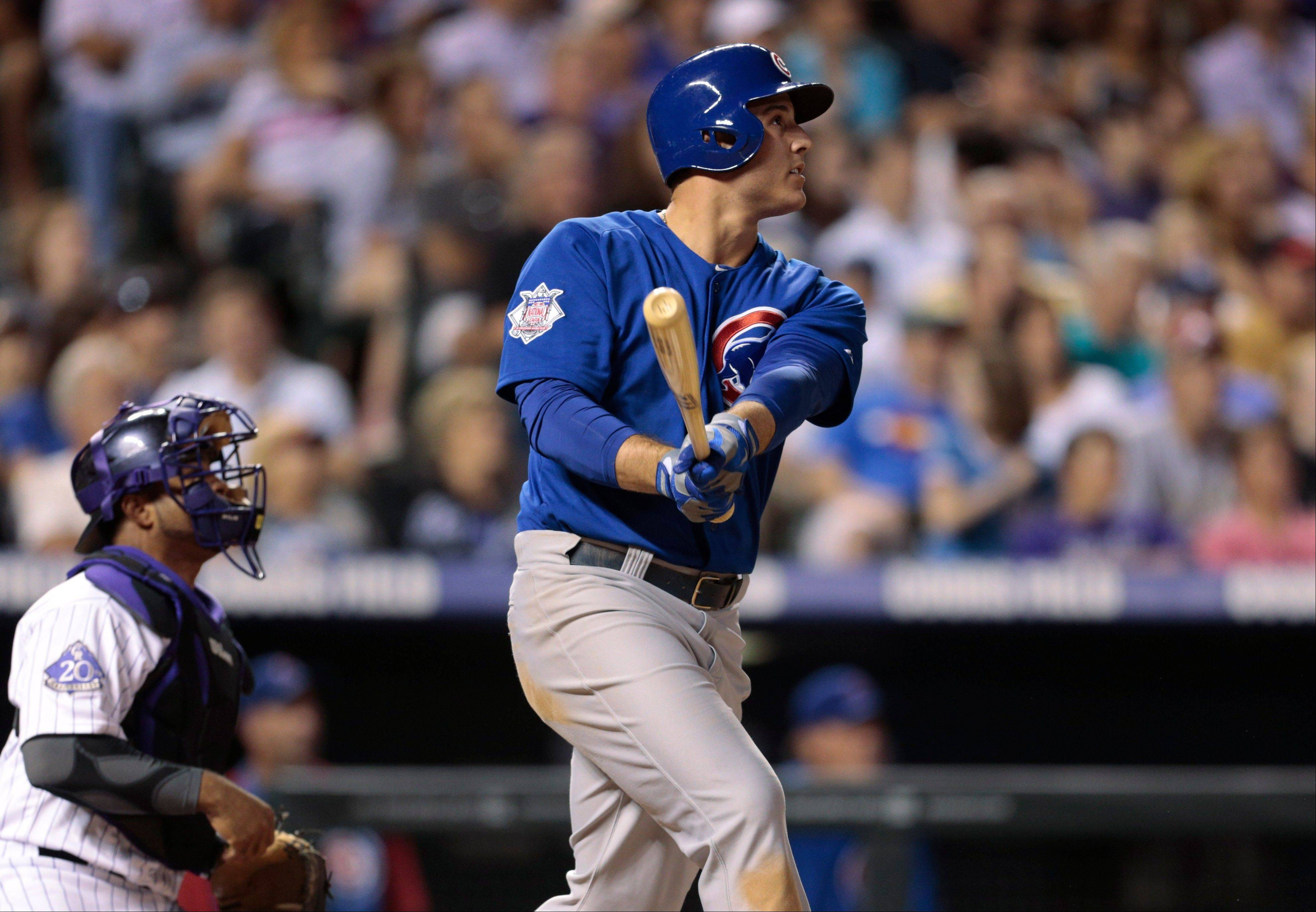 Chicago Cubs slugger Anthony Rizzo, right, and Rockies catcher Wilin Rosario watch Rizzo's fly ball in the ninth inning of the Cubs' 3-1 victory in a baseball game in Denver.