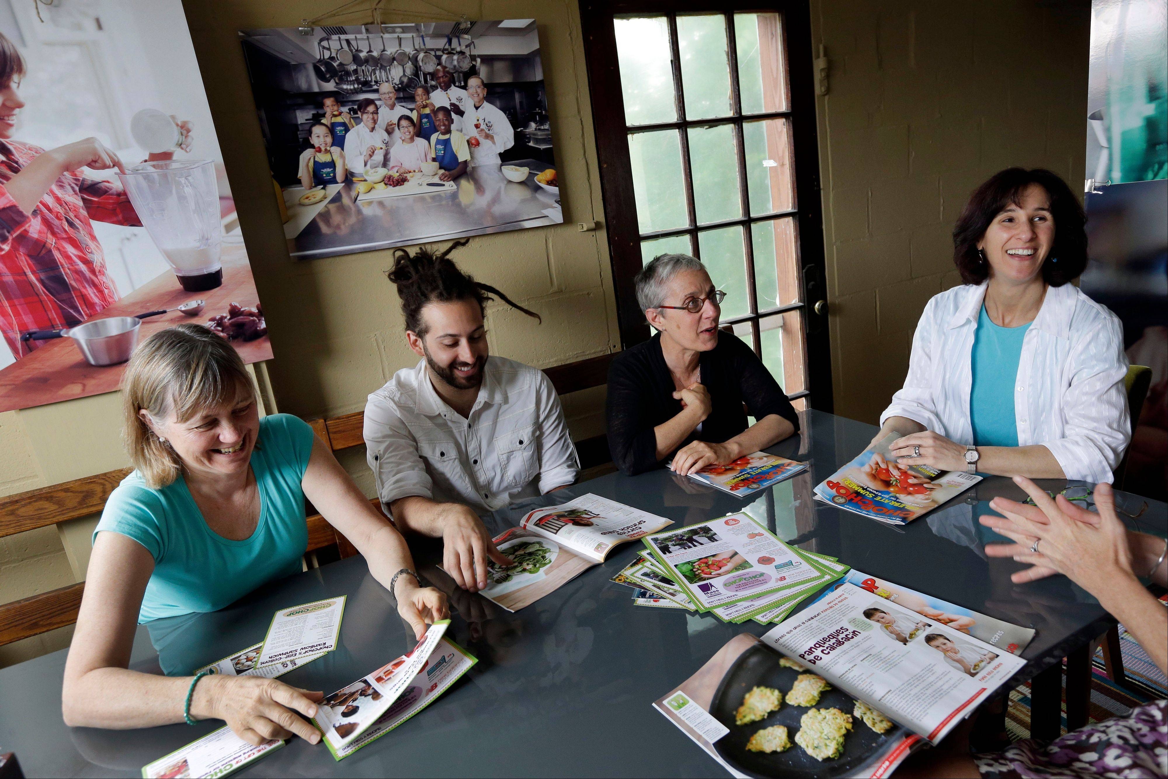 President and founder Sally Sampson, third from left, meets with staffers Cathy Chute, left, Joshua Peters, and Pamela Banks, right, around a conference table at the offices of ChopChop Magazine in Watertown, Mass.