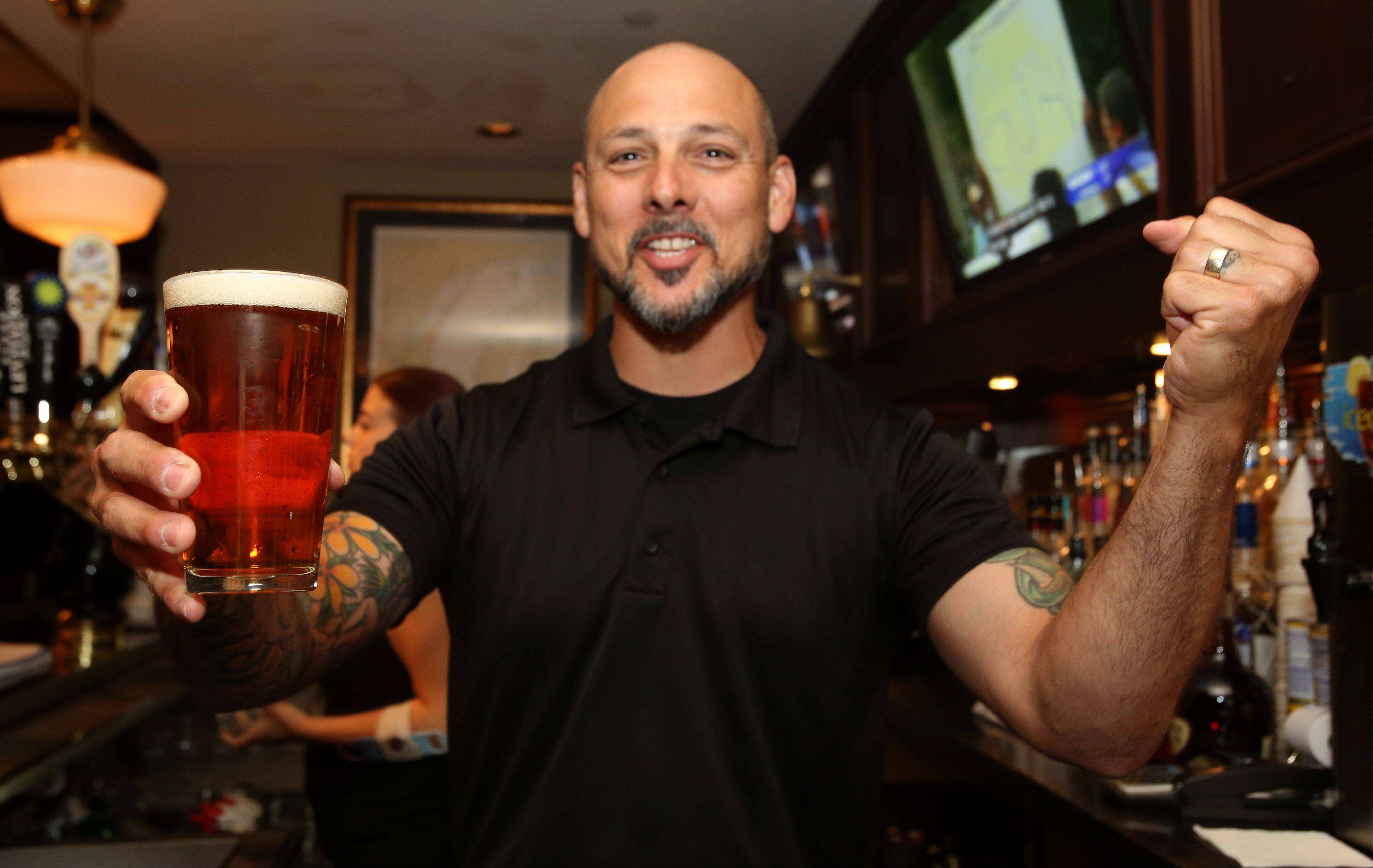 Bartender Reece Suarez serves a beer at the Wise Boxer Pour House, a new bar/club in downtown Naperville.