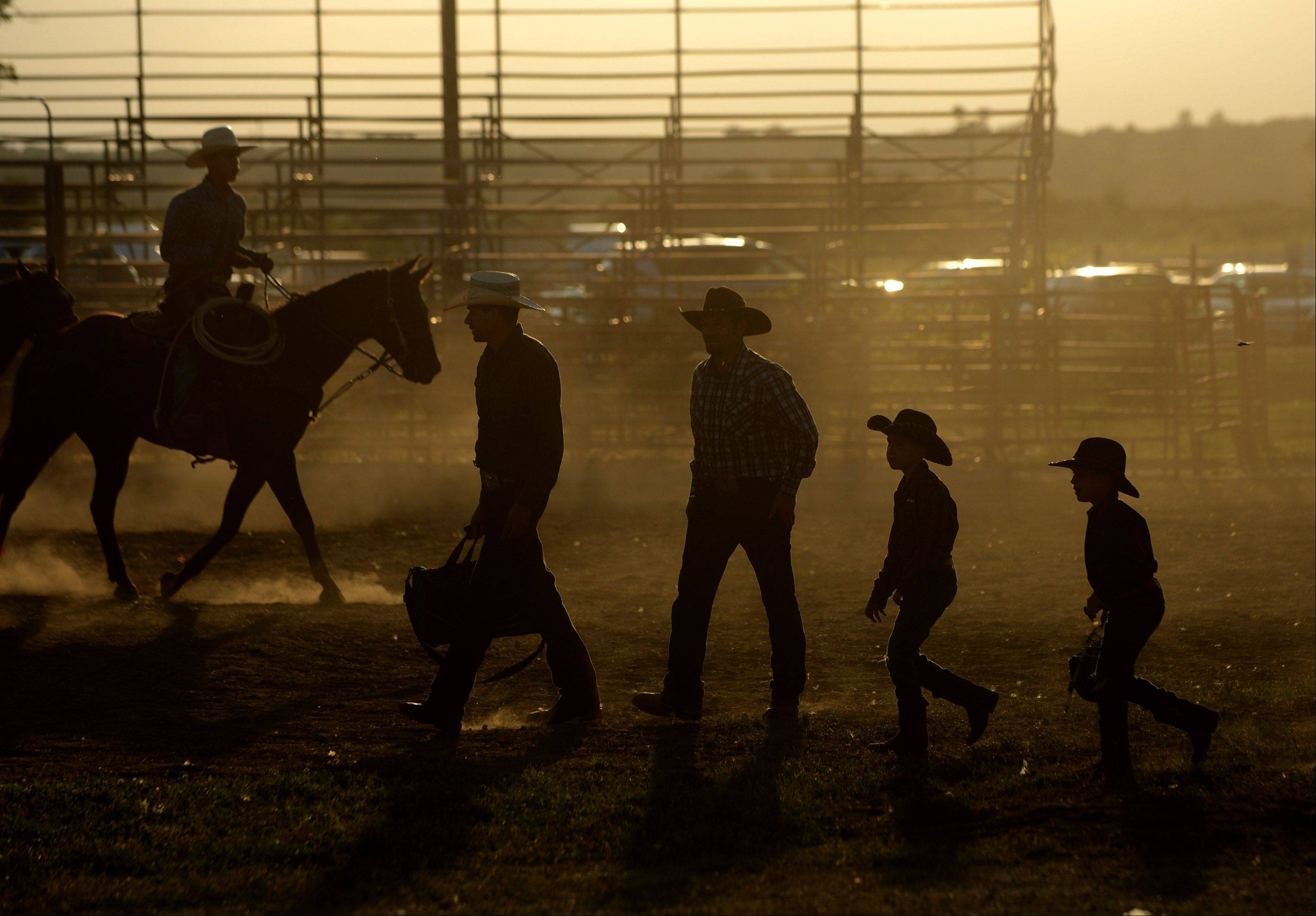 Riders and their families arrive before the Championship Bull Riding event at the Kane County Fair on Friday.