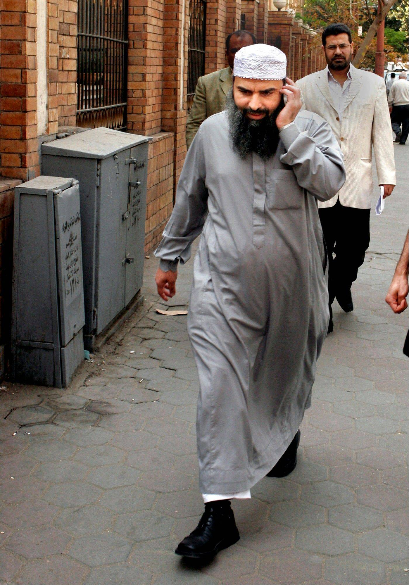 Egyptian cleric Osama Hassan Mustafa Nasr, known as Abu Omar, who was allegedly kidnapped by CIA agents off the streets of an Italian city and taken to Egypt where he said he was tortured, talks on his mobile as he walks at a Cairo street after attending Amnesty International press conference in Cairo, Egypt.