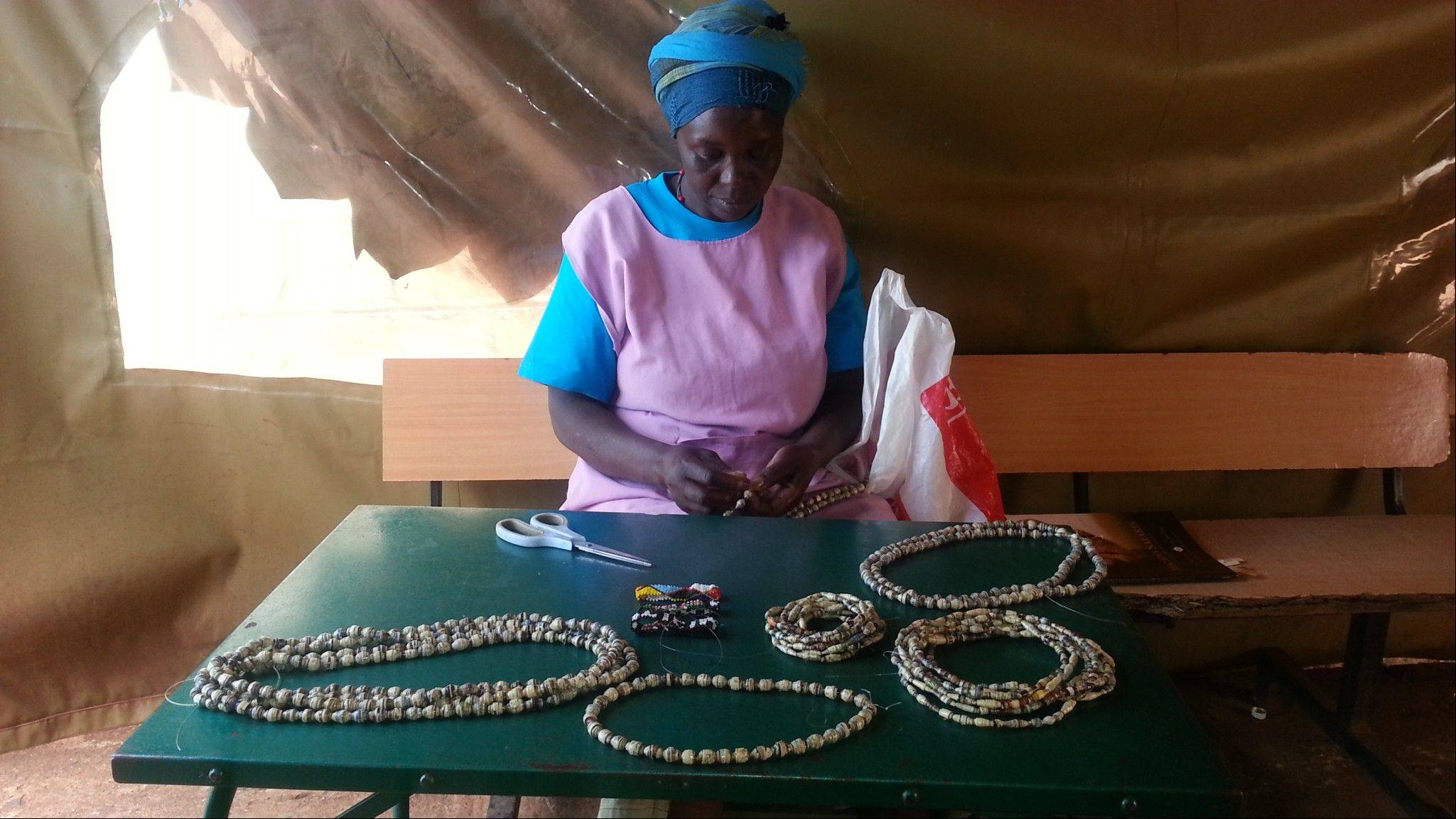 Judy making necklaces and bracelets outside of the Tabitha Clinic.