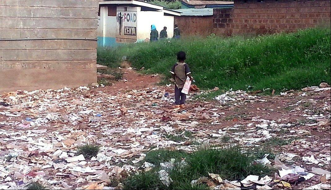 A child plays in the trash heaps outside the Kibera Primary School.