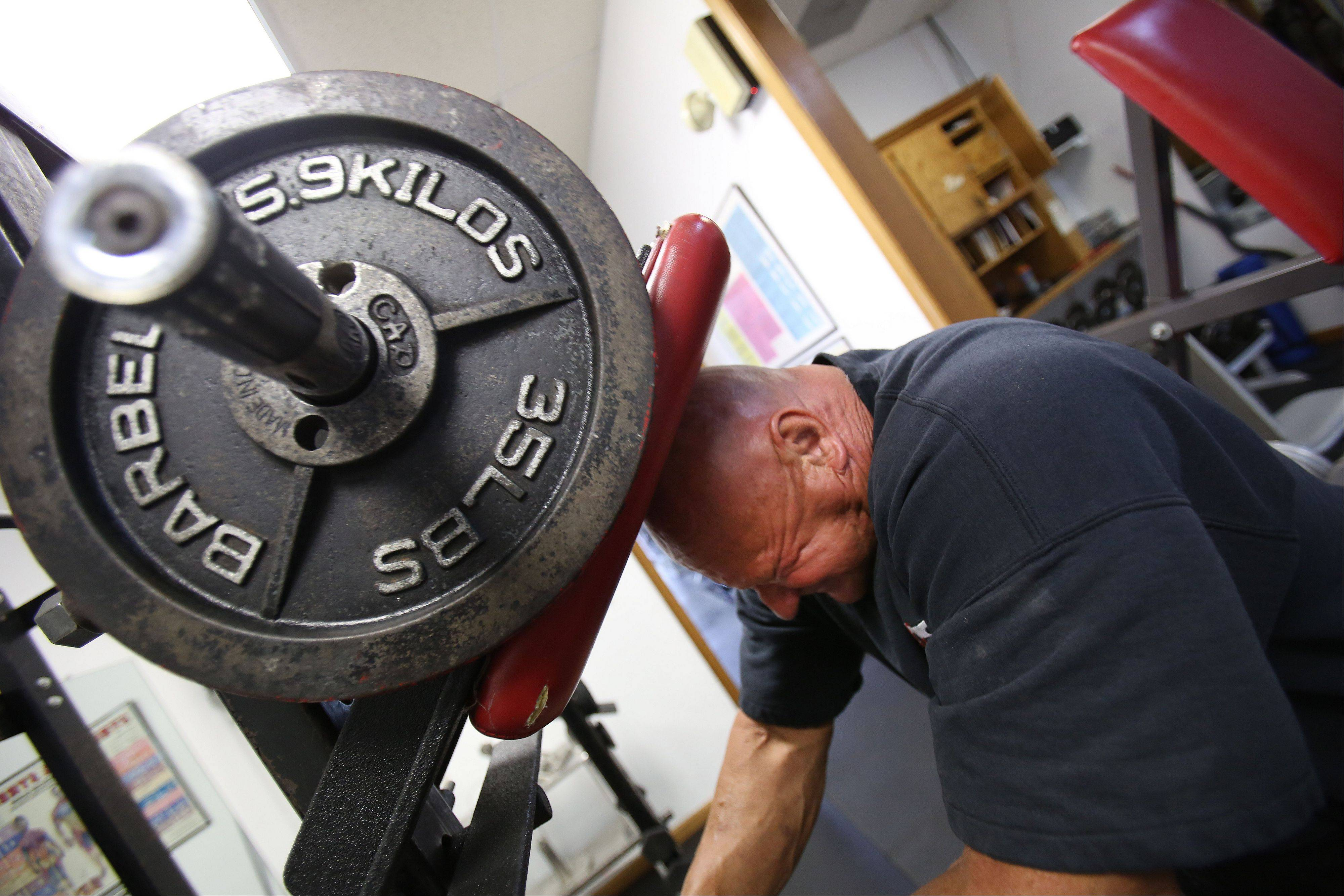 Alex Rothacker strengthens his neck on a machine he developed. He has developed several weightlifting variations.