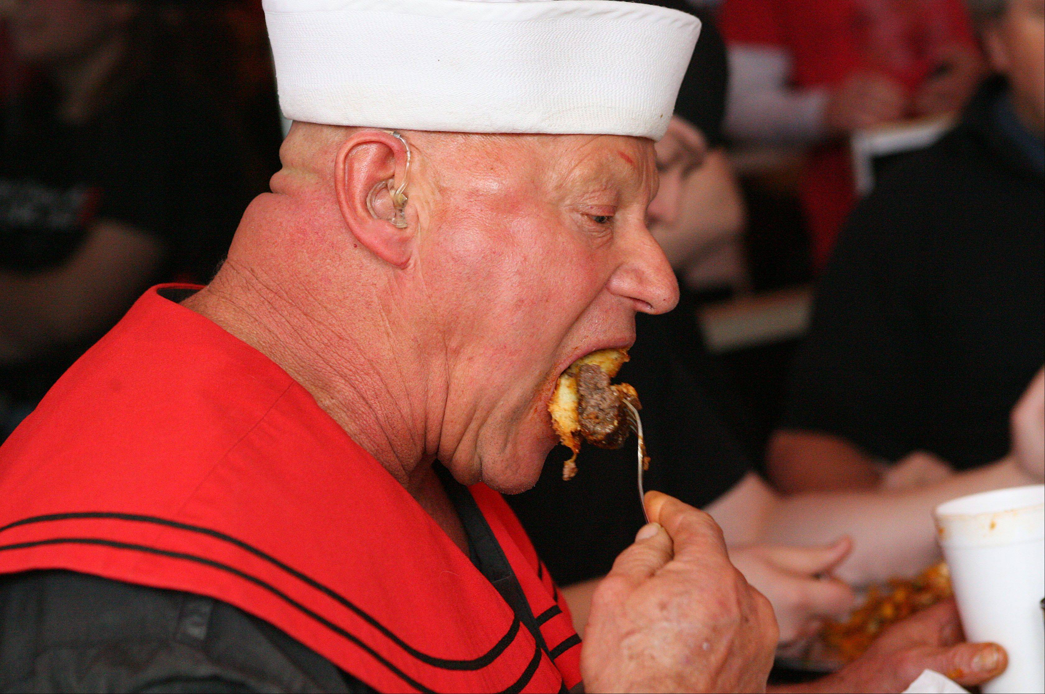 Alex Rothacker eats a four-pound hamburger in 19 minutes in an eating challenge in January at Bulldogs in Grayslake. The mammoth burger came with cheese, 12 slices of bacon and one pound of chili-cheese fries.