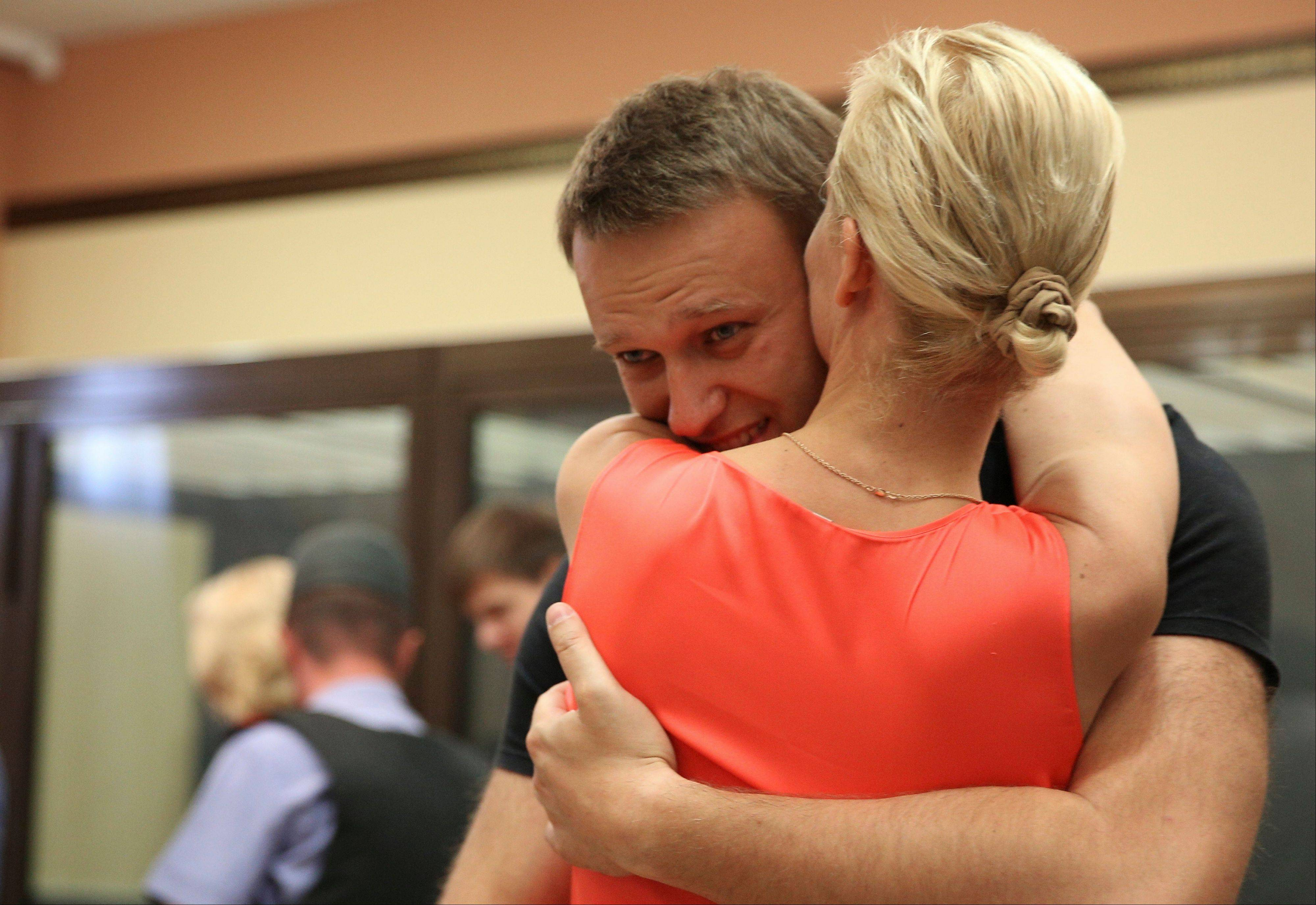 Russian opposition leader Alexei Navalny, embraces his wife Yulia, as he was released in a courtroom in Kirov, Russia Friday, July 19, 2013. A Russian court on Friday released opposition leader Alexei Navalny from custody less than 24 hours after he was convicted of embezzlement and sentenced to five years in prison. The release came after a surprise request by prosecutors, who said that because Navalny is a candidate in this fall's Moscow mayoral race keeping him in custody would deny him his right to seek election.
