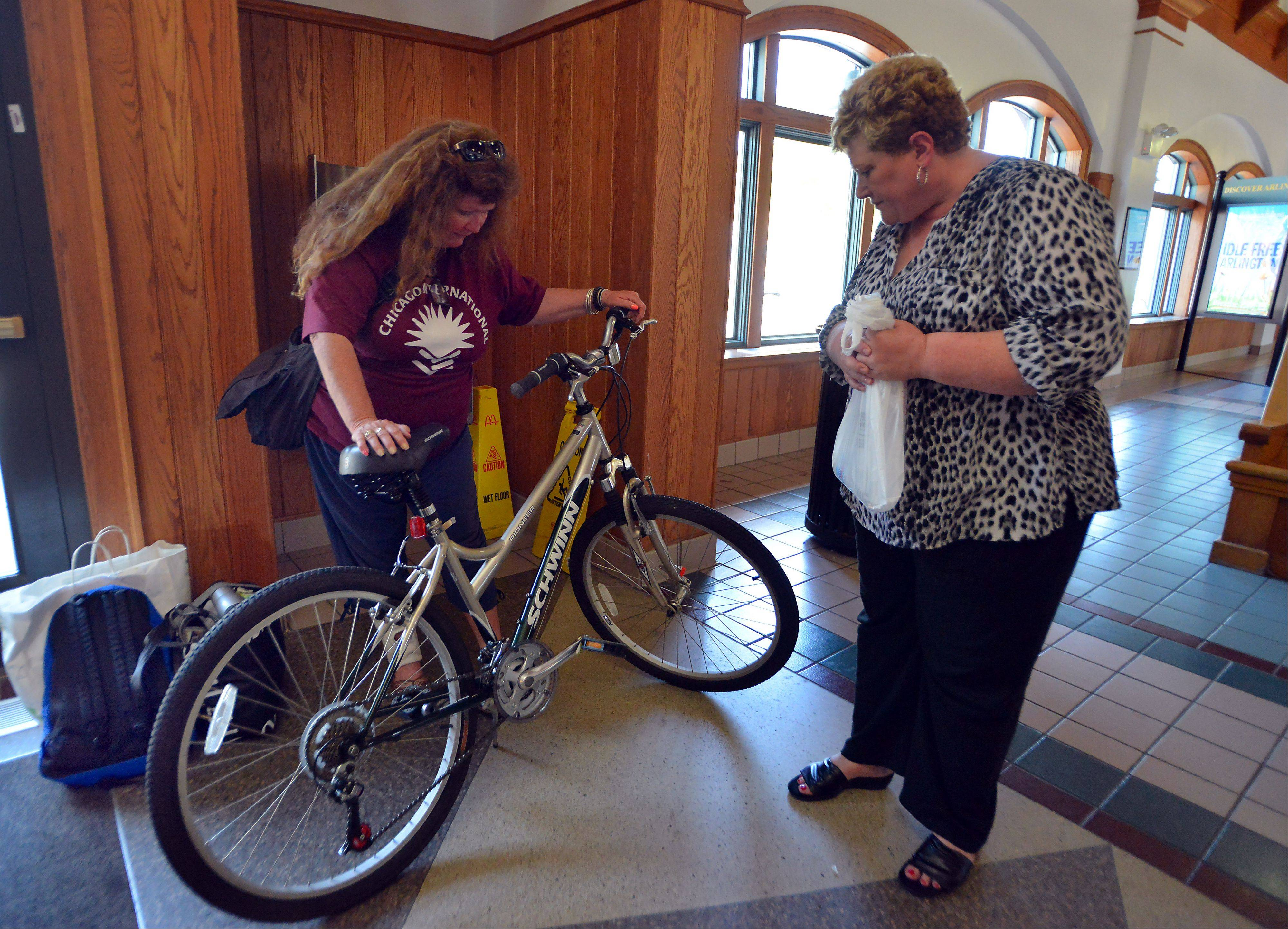 Kathy Kelly of Hoffman Estates, right, and Rosan Acosta look over the 1-year-old Schwinn bike that Kelly donated to Acosta after Acosta lost her bike and clothing in a arson fire.