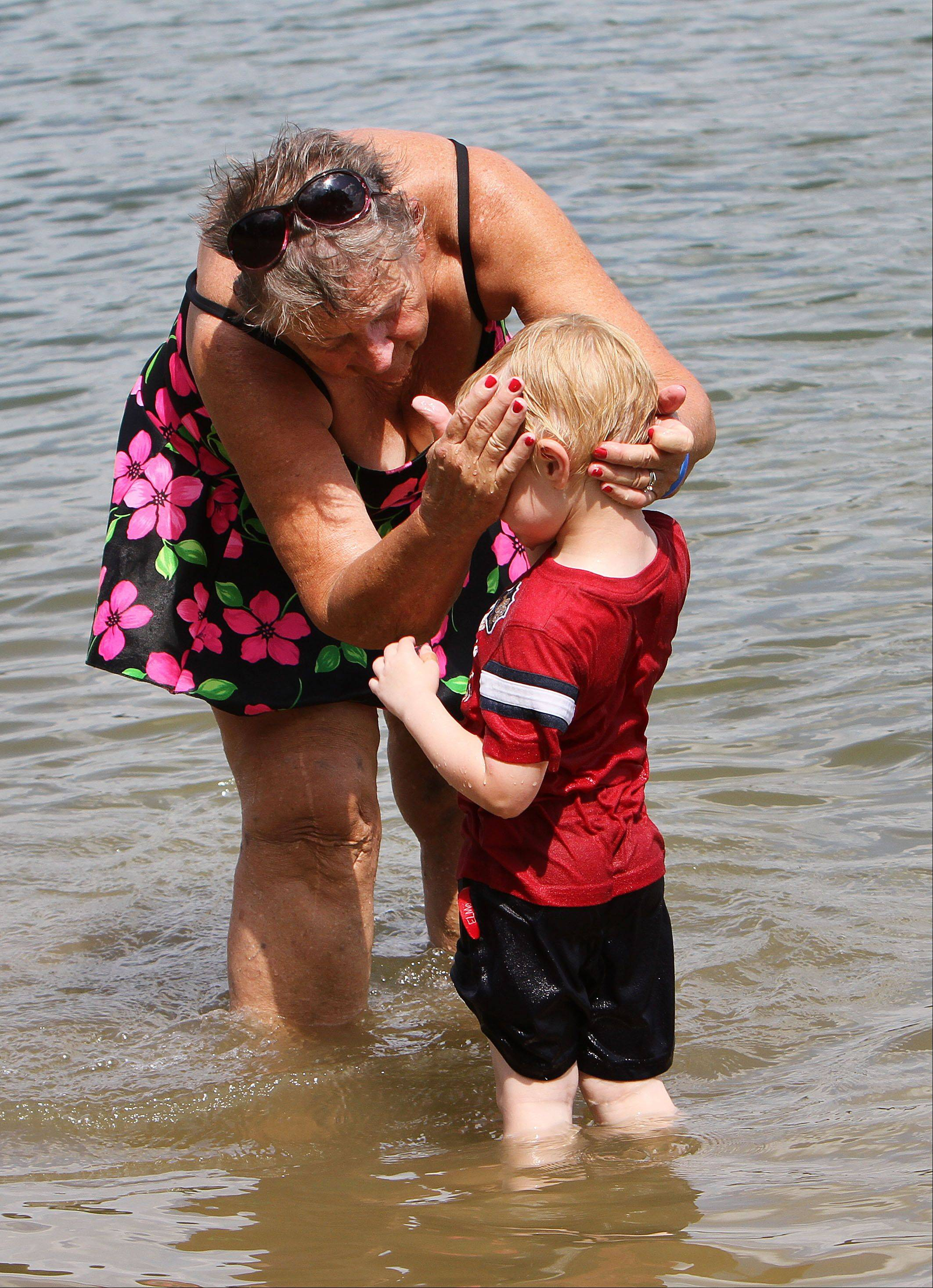 Marge Murin of Lake Zurich pours water on her grandson, Dan Murin, at Paulus Park Beach in Lake Zurich.