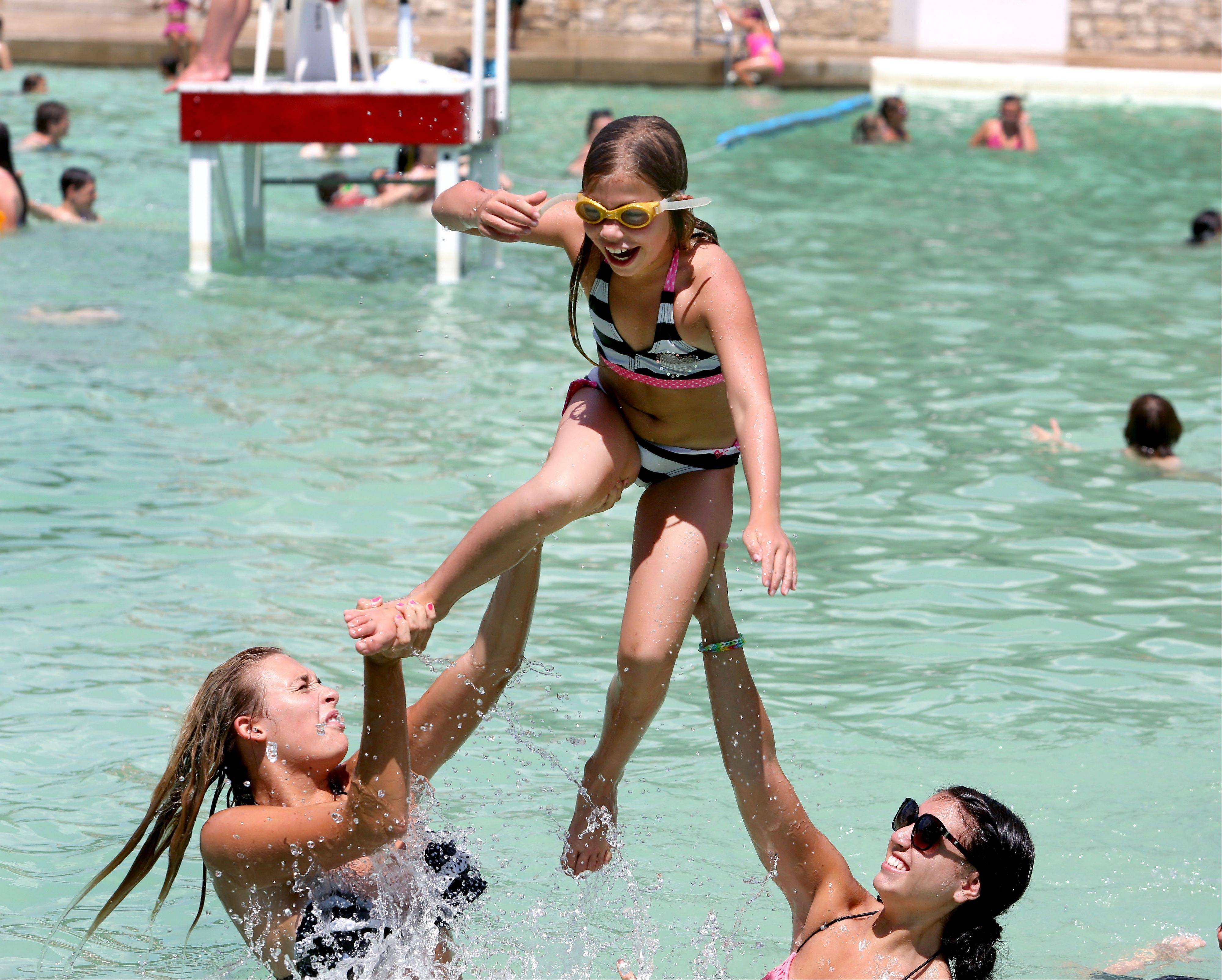 Taylor Urbanski, left, and Jackie Rubik, right, of Downers Grove give Chloe Casamassimo, 7, of Naperville a lift in the air during an outing at Centennial Beach on Thursday in Naperville.
