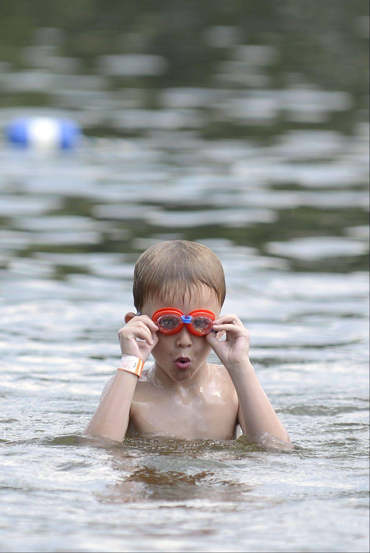 Rory Rezendes, 5, of Algonquin surfaces to adjust his googles while investigating the lake bottom at Woods Creek Lake in Lake in the Hills on Thursday. He visited the lake for the first time with his mother, Stacey, and siblings Elliot, 4, and Marshal, 1.