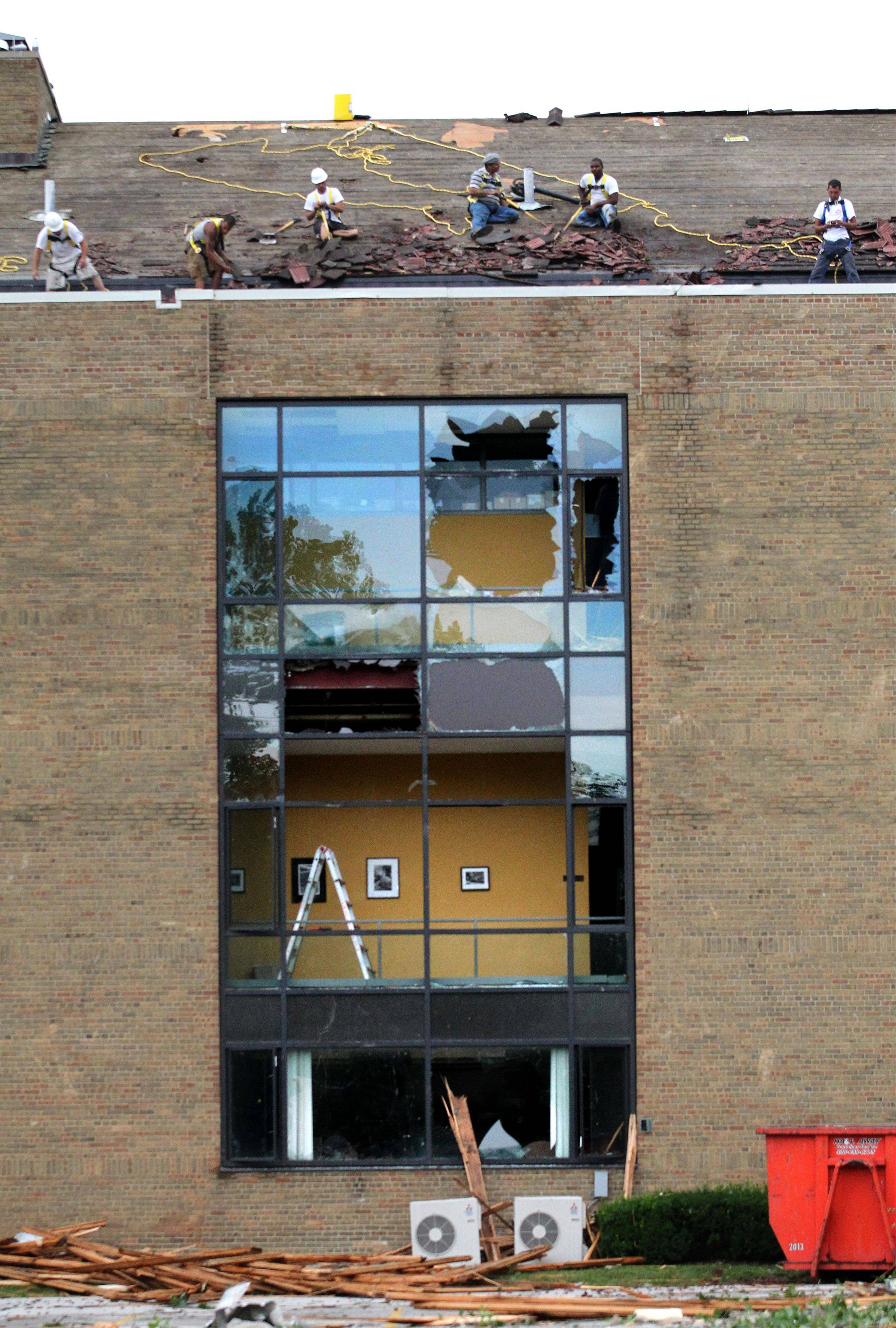Workers remove debris Saturday from the roof of the O�Brien Athletic Center on the campus of Ursuline College in Pepper Pike, Ohio.