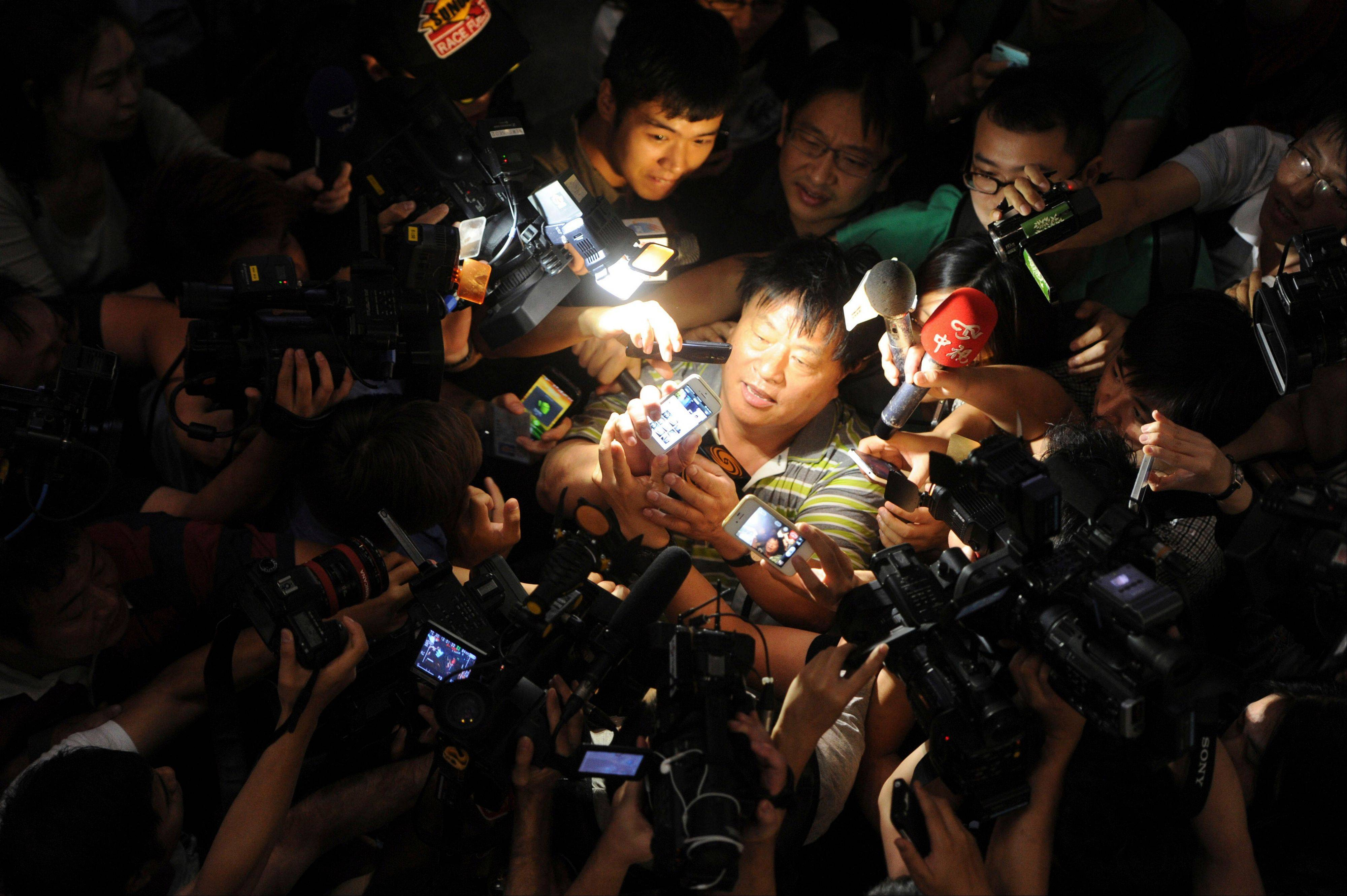 Associated Press A witness to an explosion is mobbed by journalists at Beijing International Airport�s Terminal 3, in Beijing, China, Saturday, July 20. A man on a wheelchair set off a homemade bomb at the terminal.