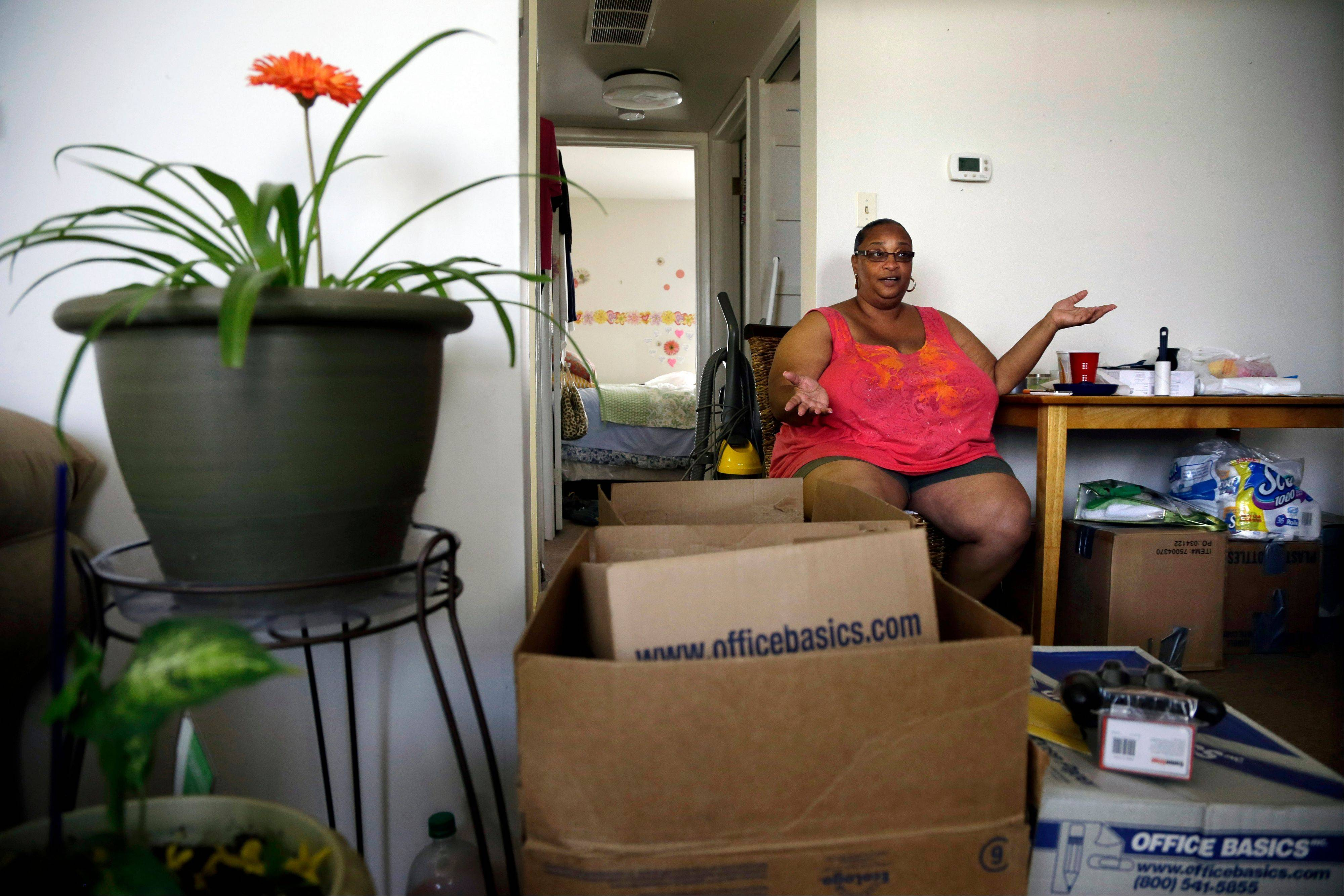 Tanya Coleman is surrounded by moving boxes as she sits