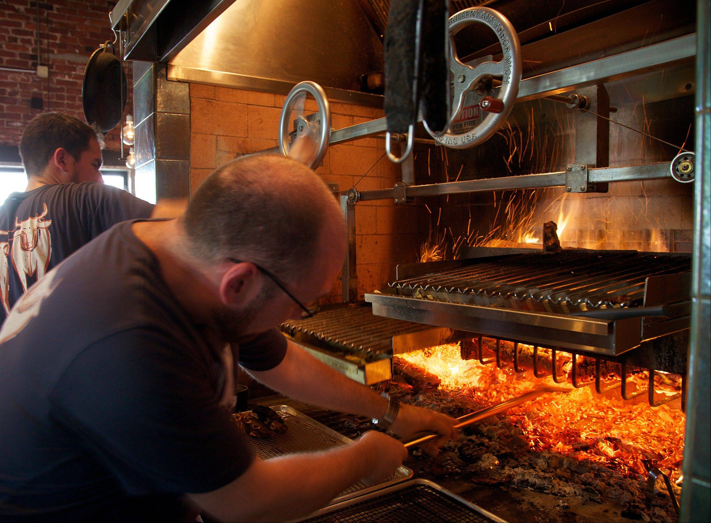 Owner and chef Greg Denton, right, checks the fire of the grill at Ox in Portland, Ore., as Patrick Martinez helps out.
