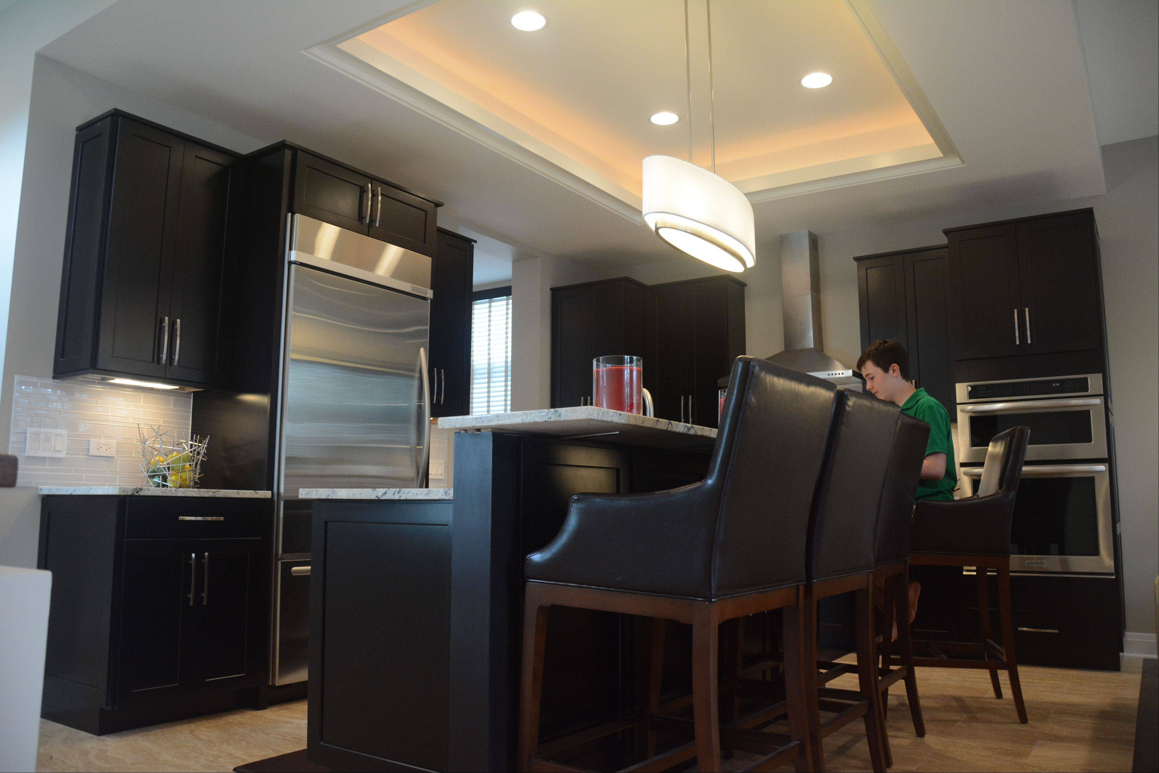 Austin Turner sits at the kitchen island near the espresso-colored cabinets his mother selected.