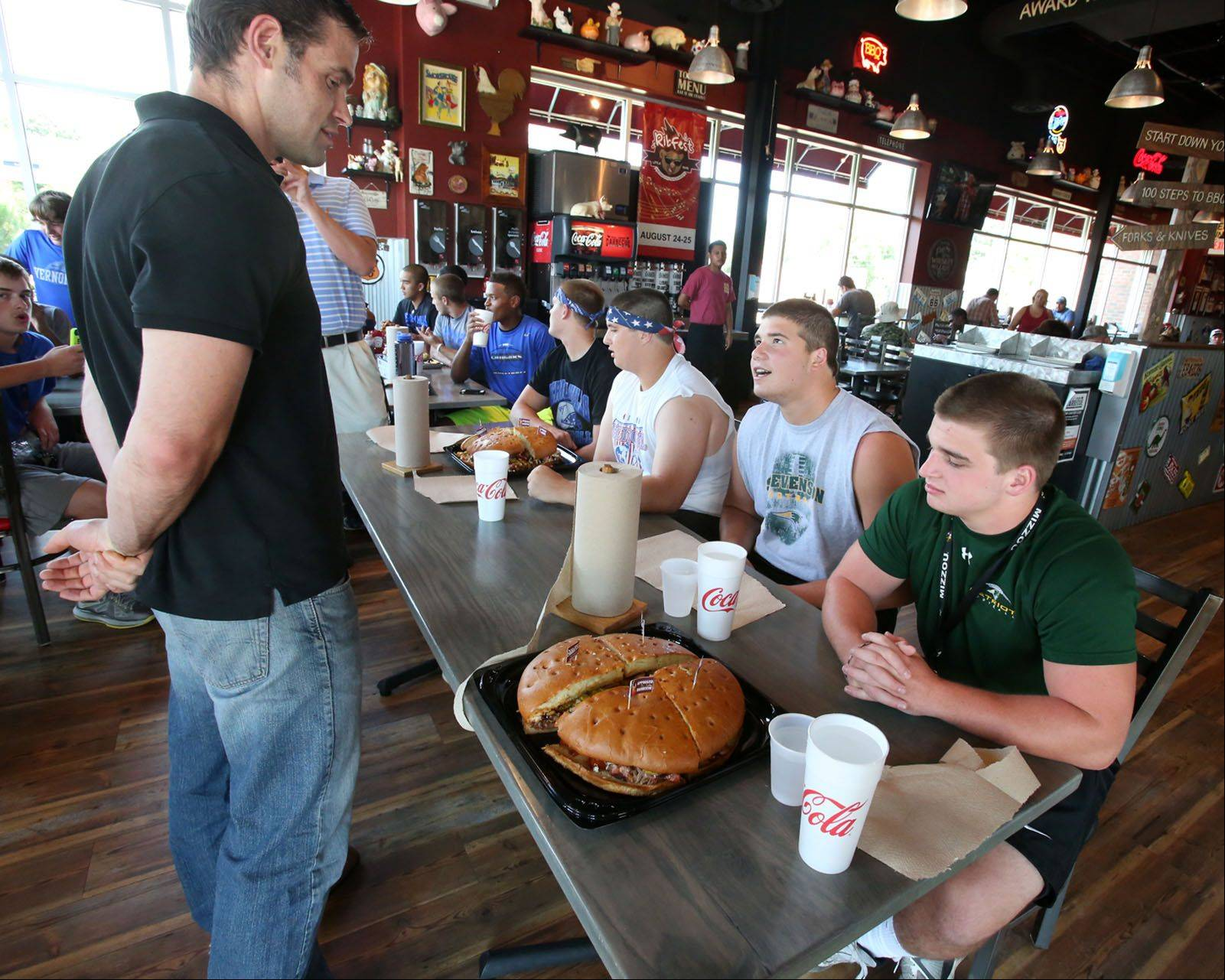 Reigning Hungry Home Wrecker champ, Jamie McDonald, coaches Stevenson High students Blake Drazner, foreground right, and Zach Novoselsky, second from right, before they compete against Vernon Hills High students Jake Campbell and Joe Blitstein, far left, in an eating contest at Real Urban Barbecue in Vernon Hills on Saturday.