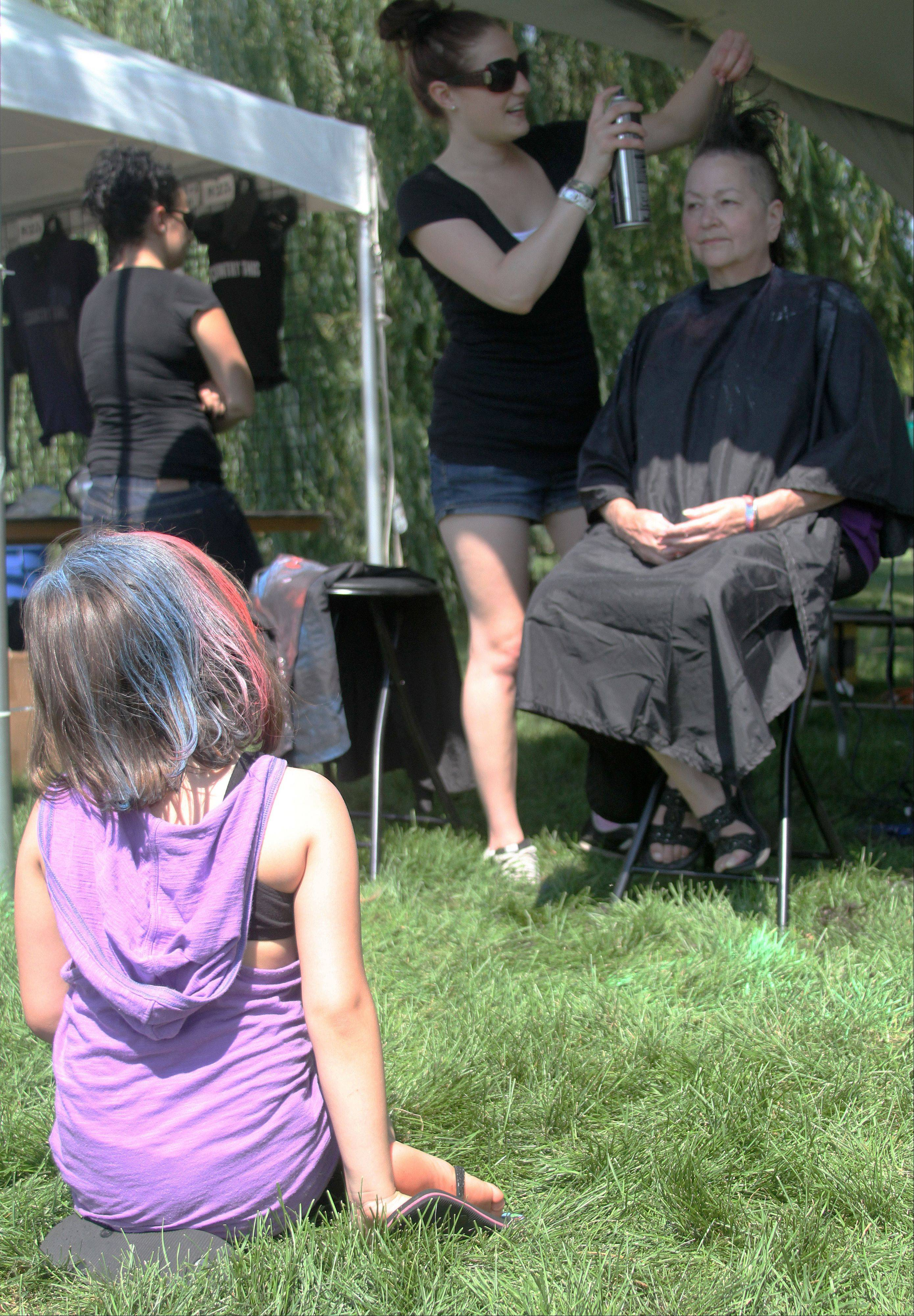 "After getting her hair colored, Halie DeVries, 7, of Alsip, left, watches her grandmother, Bonnie Dymanus of Alsip, get her head shaved into a mohawk and colored at the Apex ""Shave the Nation"" booth at the annual Rockin' for the Troops concert Saturday at Cantigny Park in Wheaton. Dymanus' husband is an Air Force veteran."