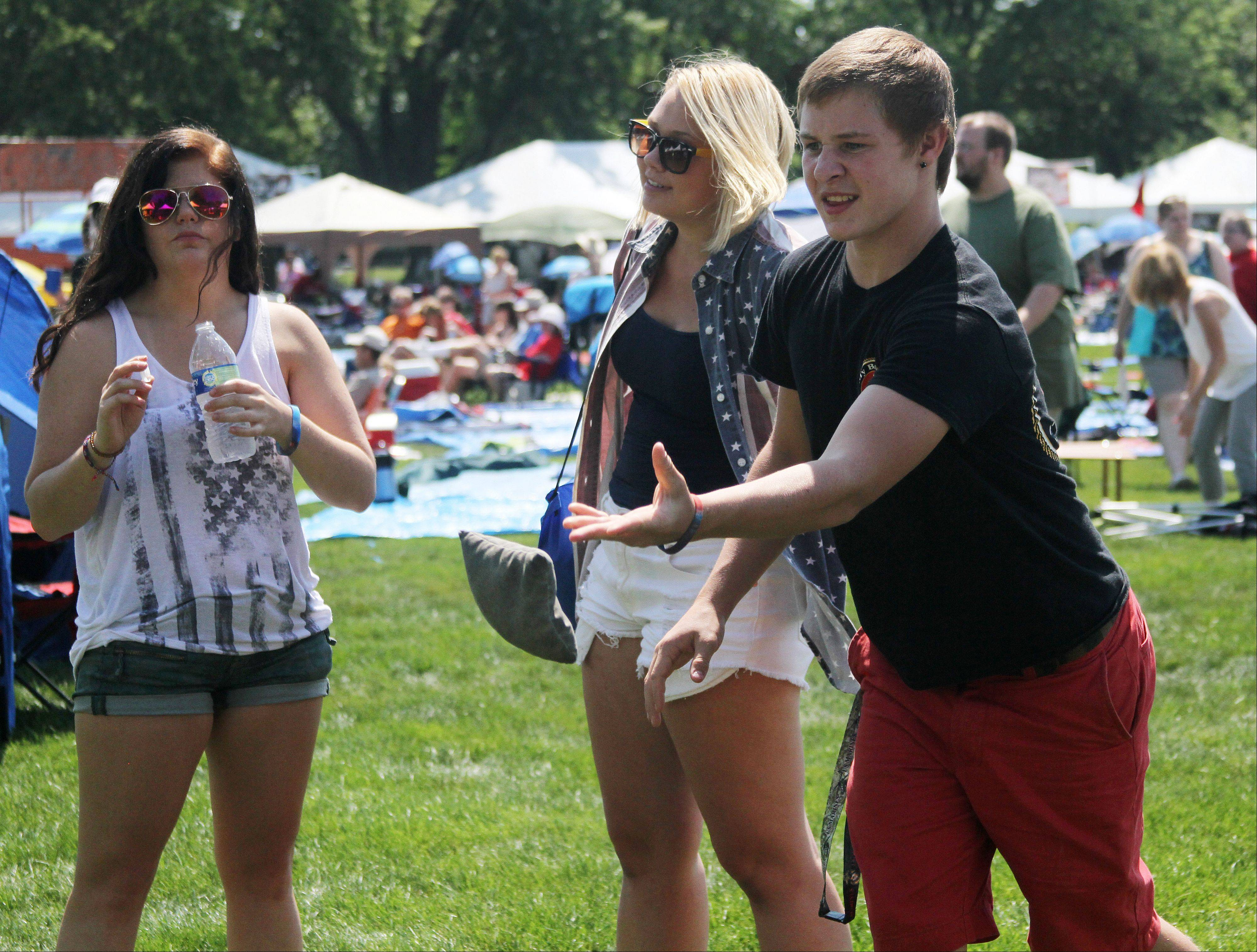 Andrea Esposito of Oak Lawn, left, and Sami Burton of Mount Prospect, center, watch as Ryan McLaughlin of Mount Prospect plays bags at the 95.5 The River booth at the annual Rockin' for the Troops concert Saturday at Cantigny Park in Wheaton.