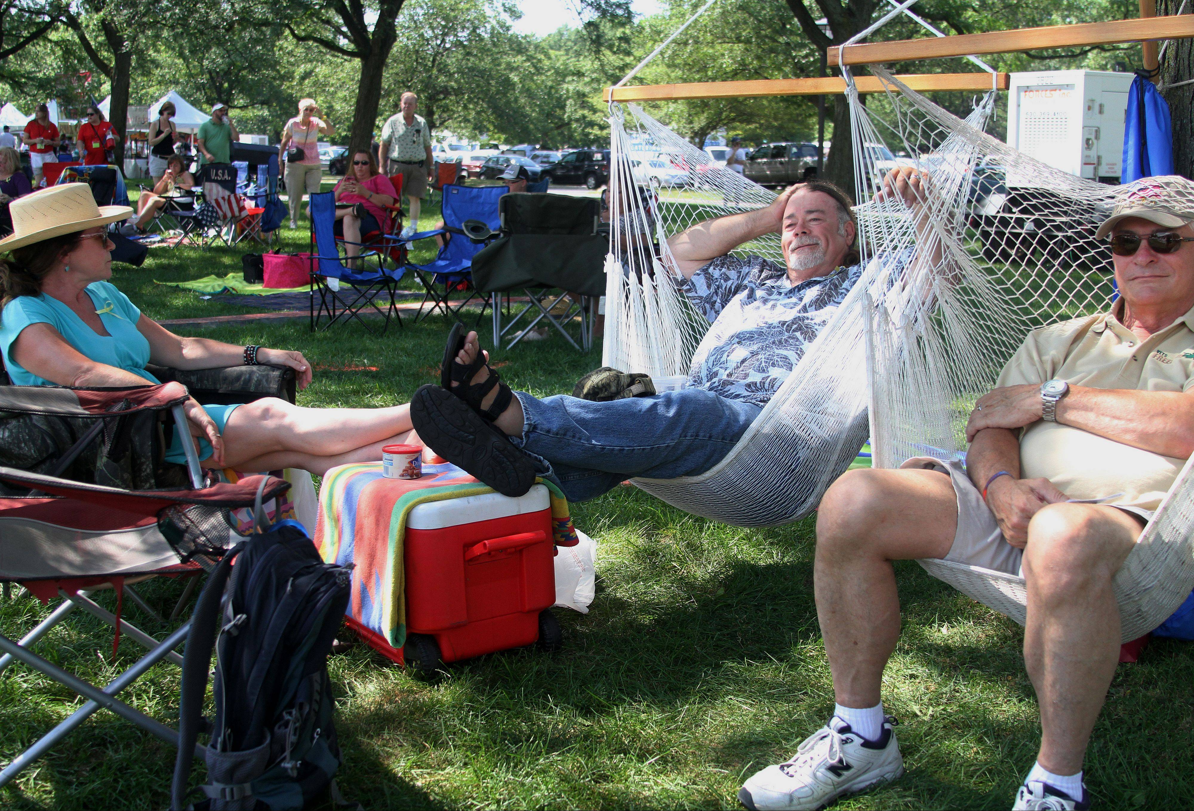 "Rick McInnes, center, and Don Castella, left, sit in McInnes' invention ""The Perched Pelican"" while Lauren McInnes sits in a lawn chair at the annual Rockin' for the Troops concert to benefit Operation Support Our Troops -- American on Saturday at Cantigny Park in Wheaton."