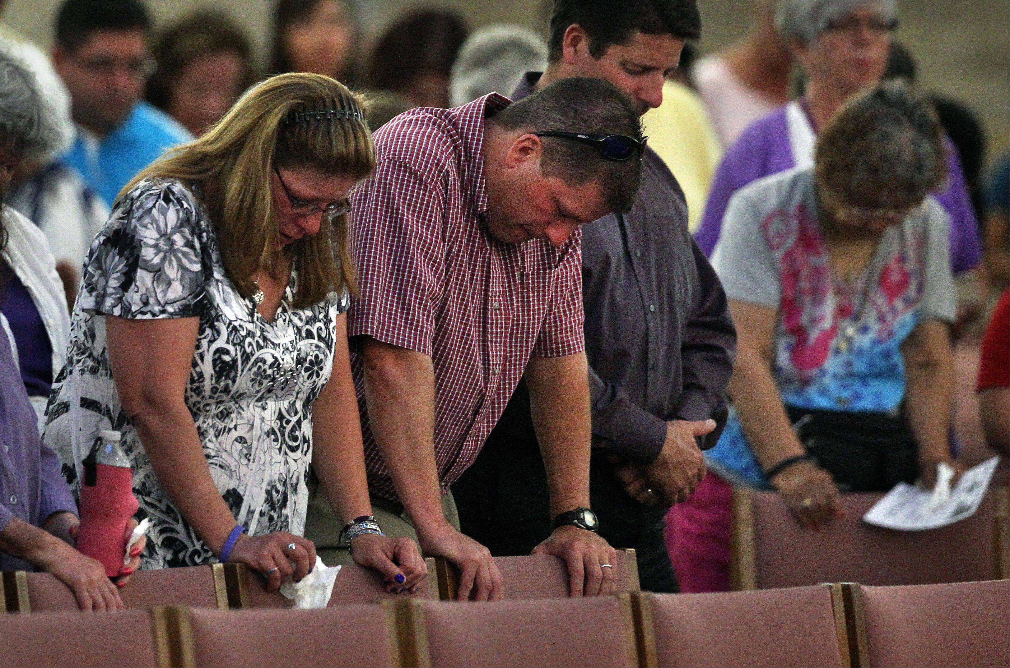 Associated PressWorshippers attend a memorial mass held for supporters and families of those killed in the Aurora movie theater shootings, at St. Michael the Archangel Catholic Church, in Aurora, Colo., on Friday July 19. Saturday, July 20, marks one year since the theater killing rampage left 12 dead and 70 wounded.