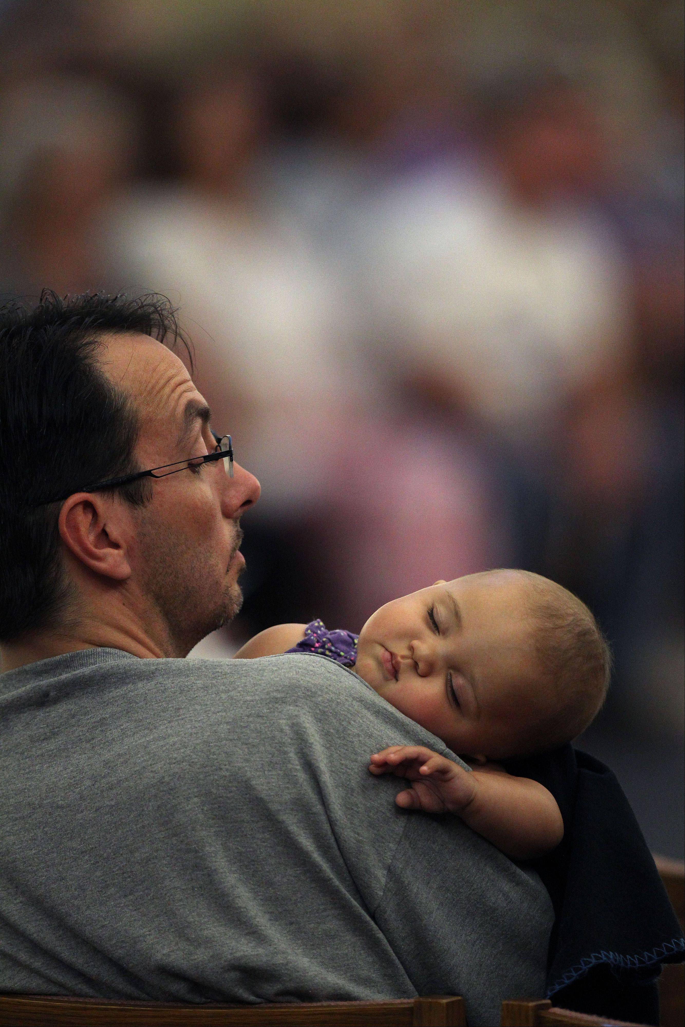 Associated PressA man checks on his baby during a memorial mass held for supporters and families of those killed in the Aurora movie theater shootings, at St. Michael the Archangel Catholic Church, in Aurora, Colo., on Friday July 19. Saturday, July 20, marks one year since the theater killing rampage left 12 dead and 70 wounded.