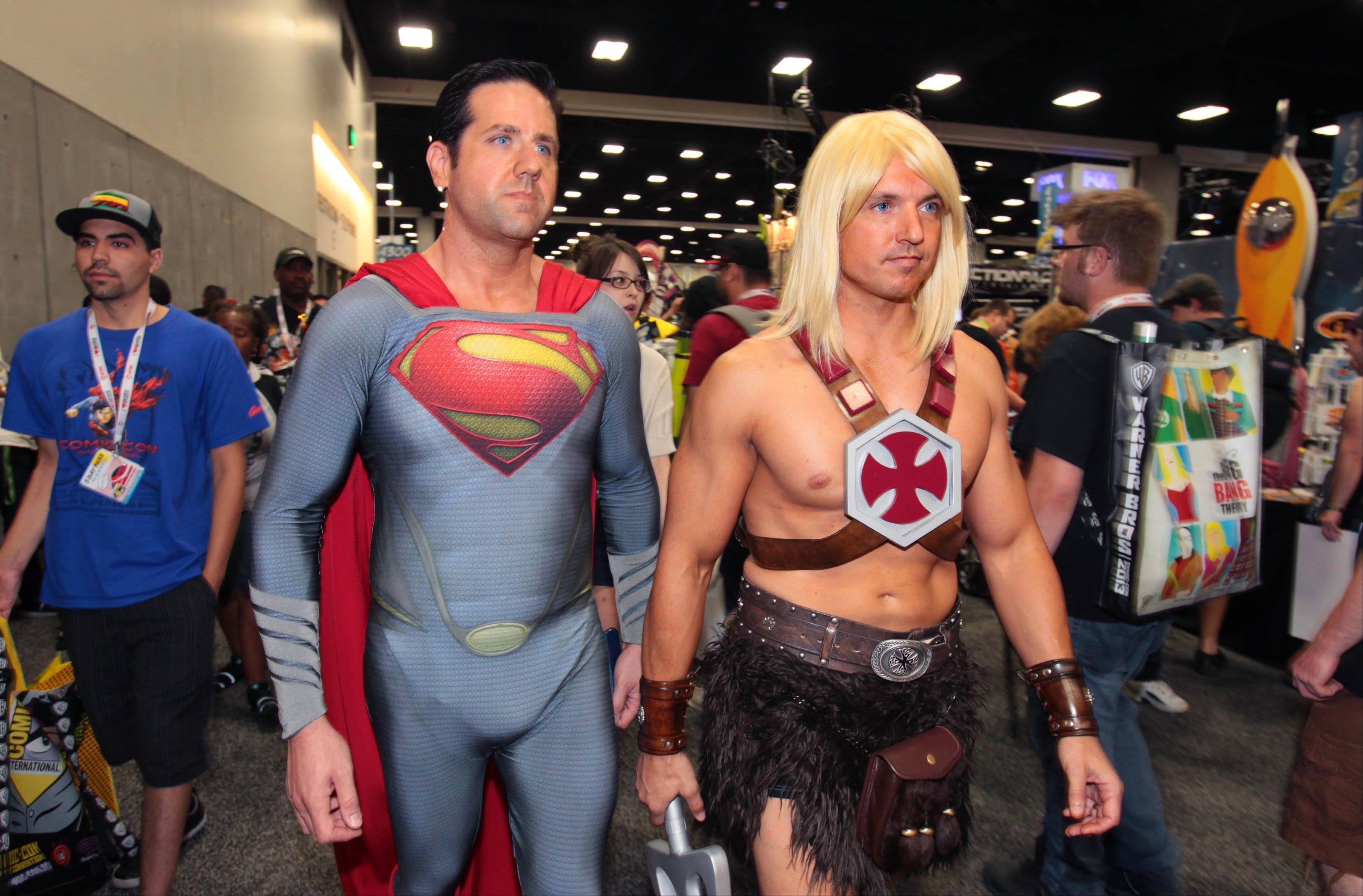 In this Thursday, July 18, 2013 photo, Arizona natives Trey Moore, left, dressed as Superman, and Ben Dickinson, dressed as He-Man, walk through the main exhibit hall at Comic-Con International in San Diego.