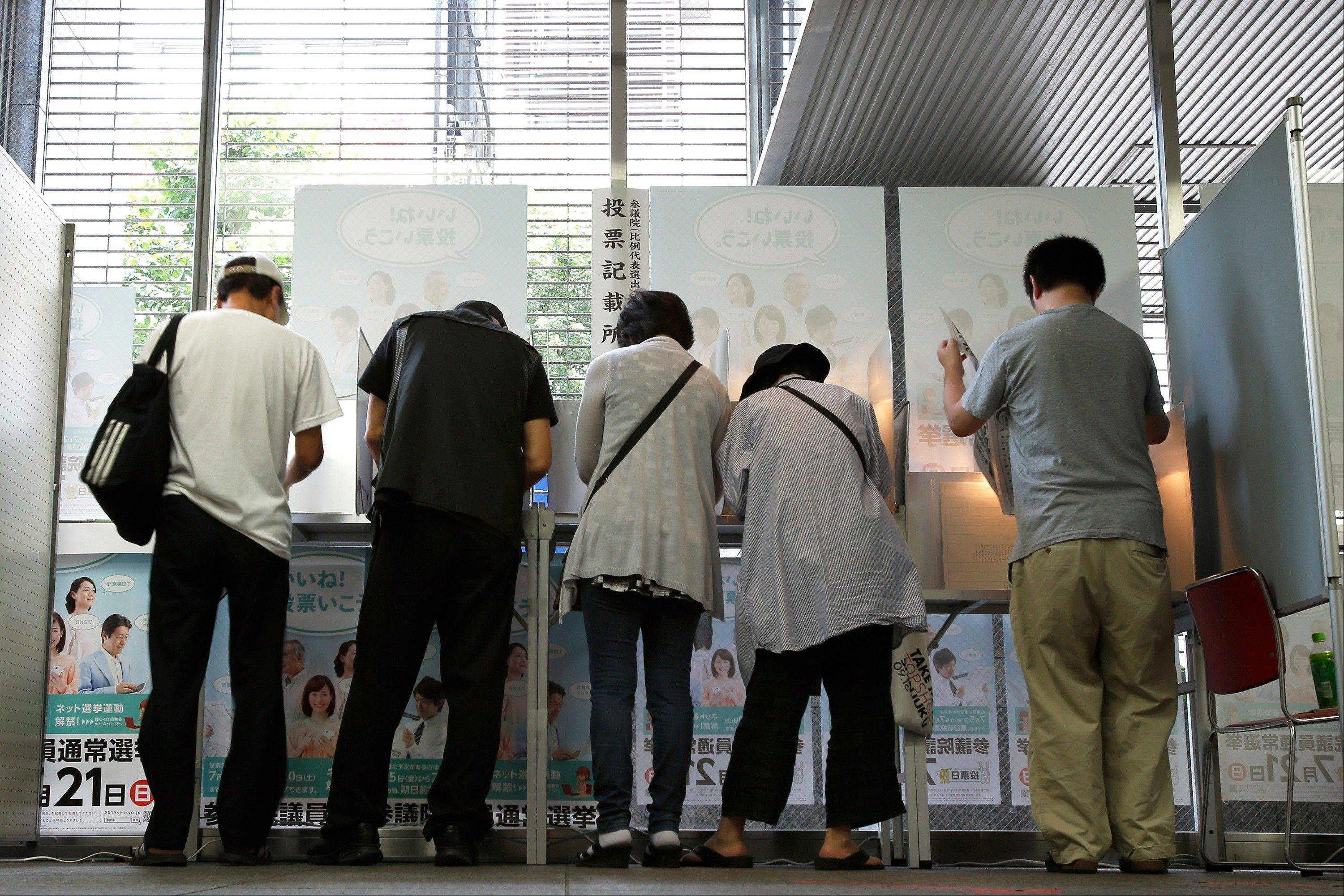 Voters fill out their ballots for the Japanese parliament�s upper house election at a polling station in Tokyo, Japan, on Sunday, July 21, 2013. Japanese voters are set to hand Prime Minister Shinzo Abe control of both houses of Parliament, giving him a mandate to extend his overhaul of the world�s third-biggest economy.
