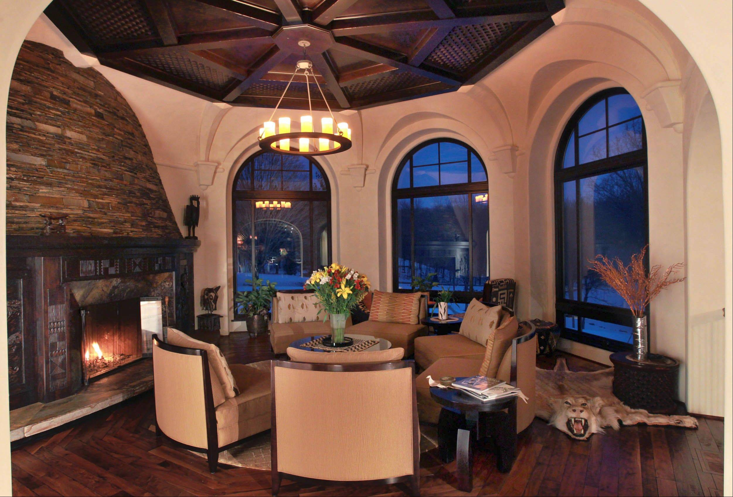 The round living room features a curved drystack stone fireplace.