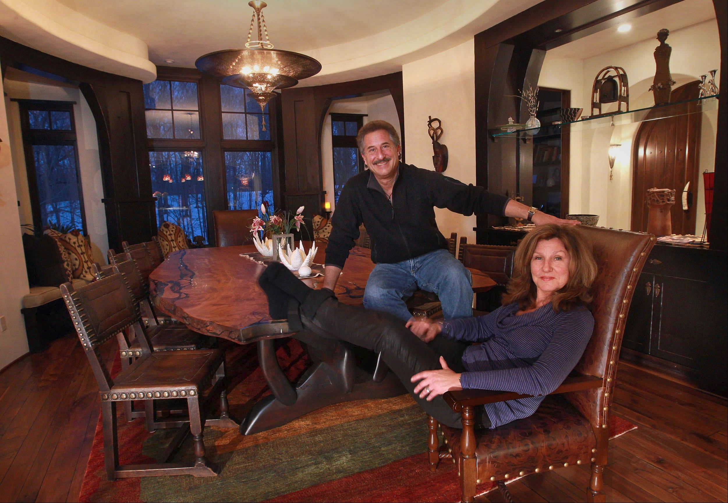 Cass and Andy Stillman, relaxing above in their dining room, built a home with architectural details inspired by their love of Africa.