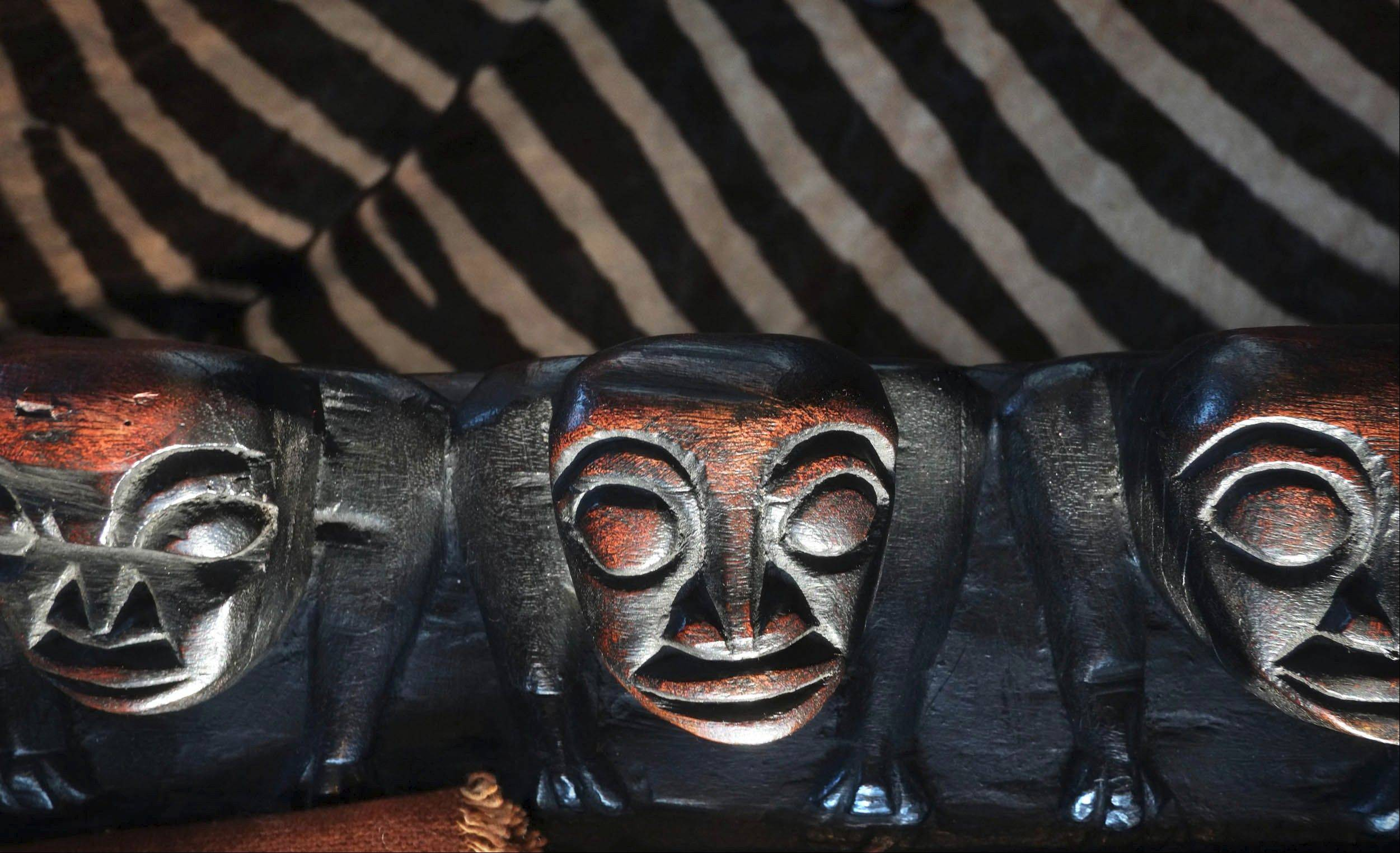 An antique pygmy bed from Cameroon, with carved faces along its edge, now serves as a coffeetable.