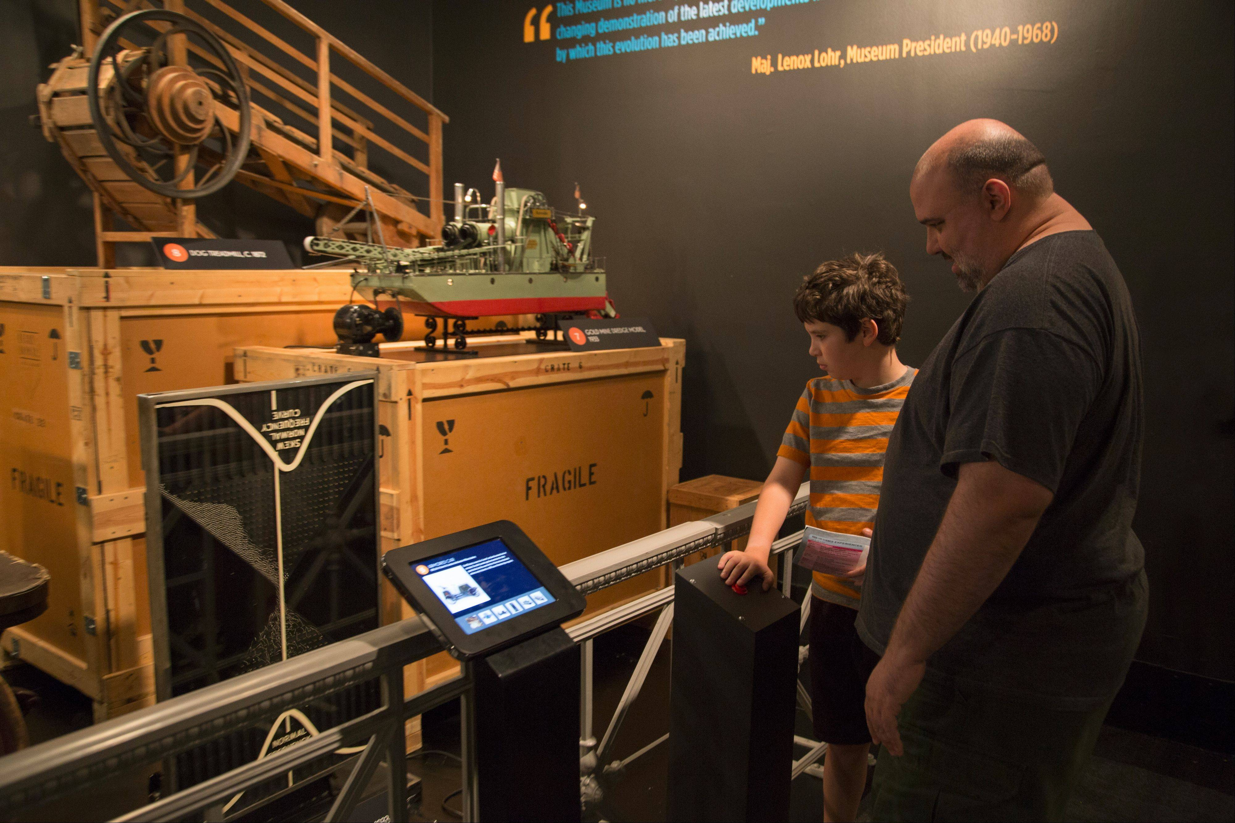 Two guests study the Galton Quincunx, a probability machine developed by Sir Francis Galton, dating back to 1933.