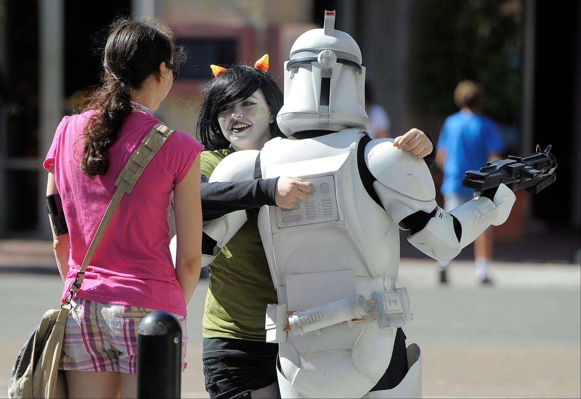 "Comic-Con attendees, including one dressed as a ""Star Wars"" Clone Trooper, greet each other outside the 2013 Comic-Con International Convention on Wednesday, July 17, in San Diego."