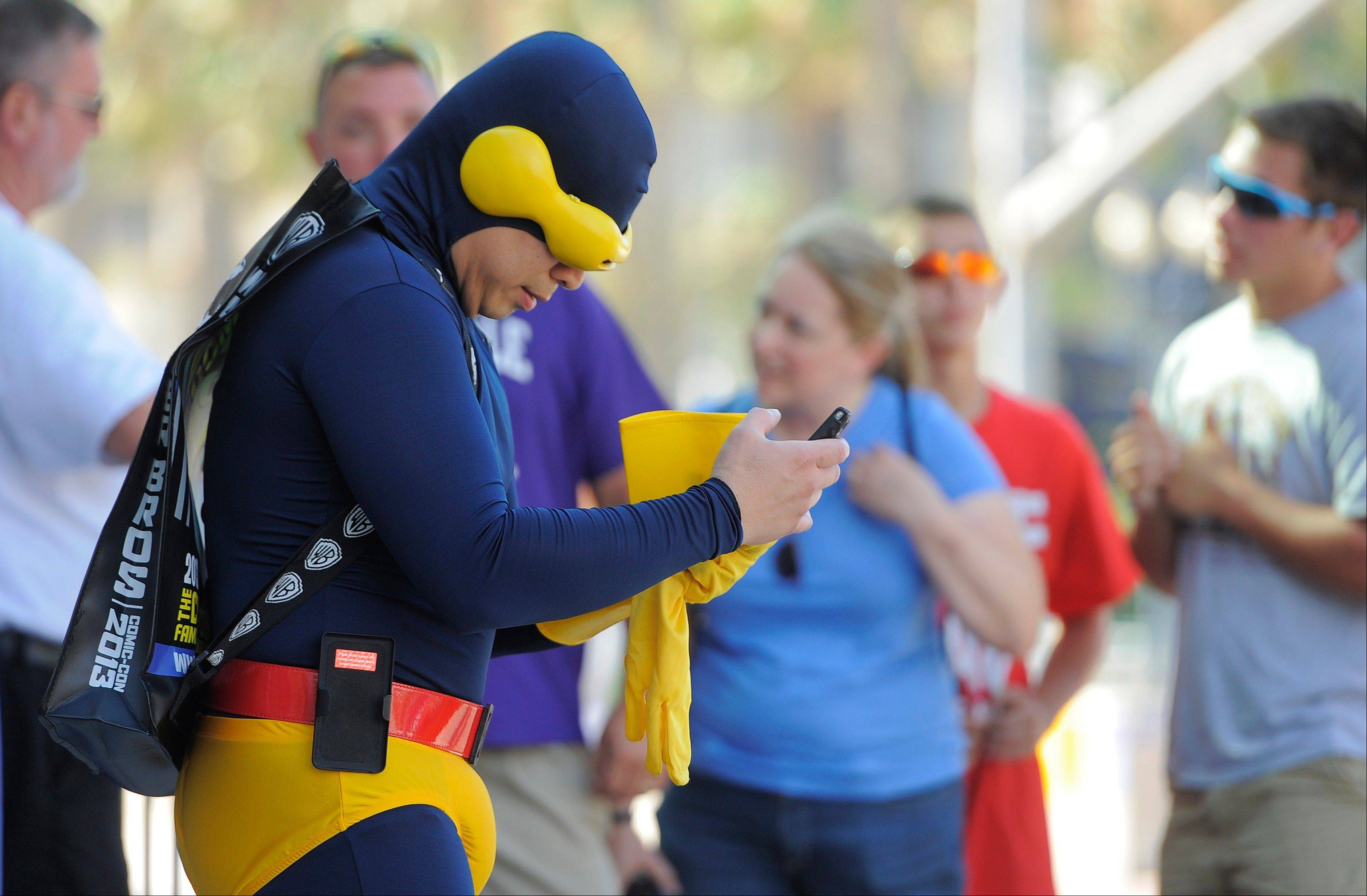 Cyclops of the X-Men -- aka Gene Ross of Chula Vista, Calif. -- checks his cell phone as he stands outside the 2013 Comic-Con International Convention on Wednesday, July 17, in San Diego, Calif.