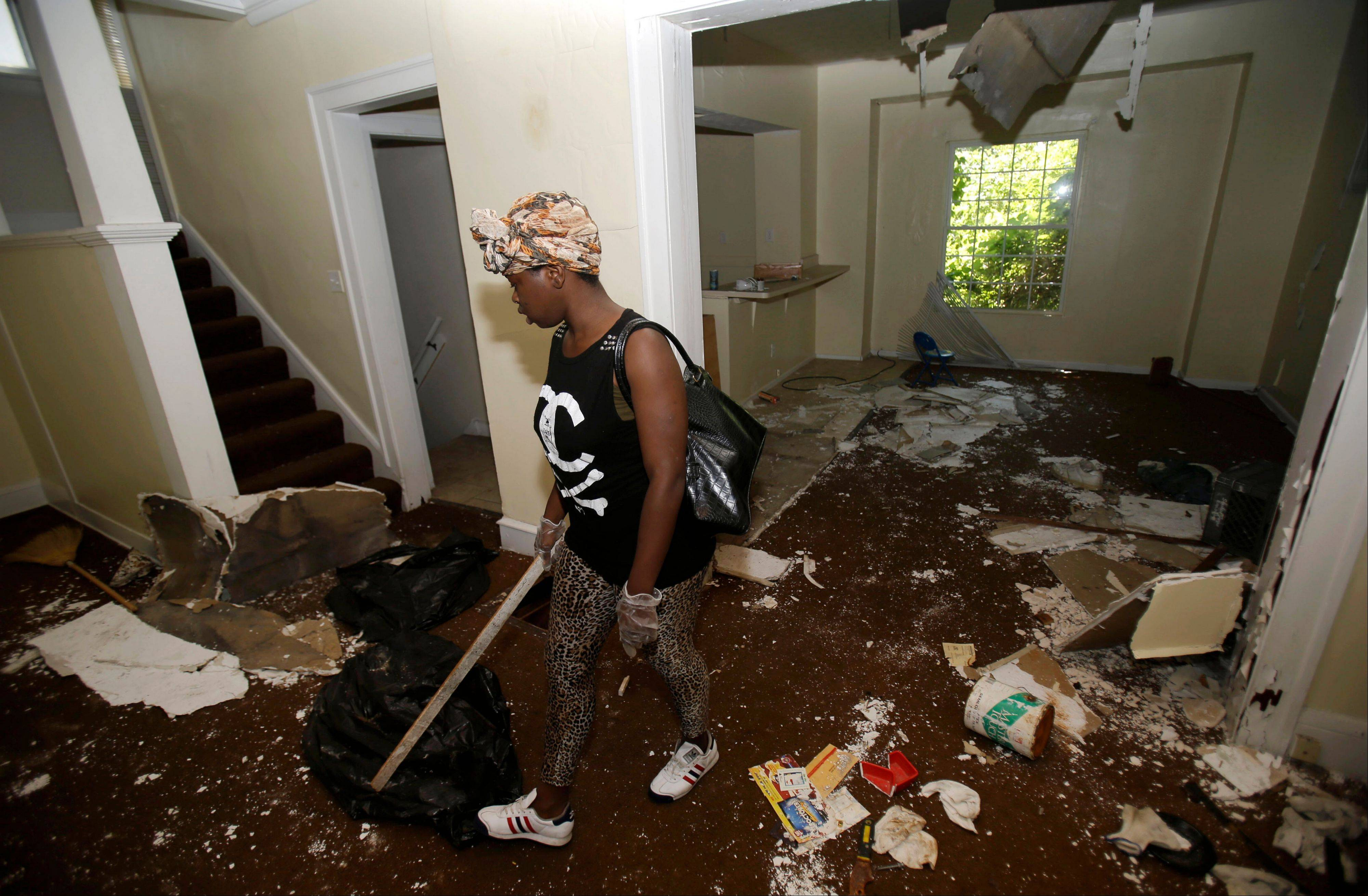 Sanautica Hicks-Ross, 18, searches an abandoned home Sunday near where three bodies were found in East Cleveland, Ohio.