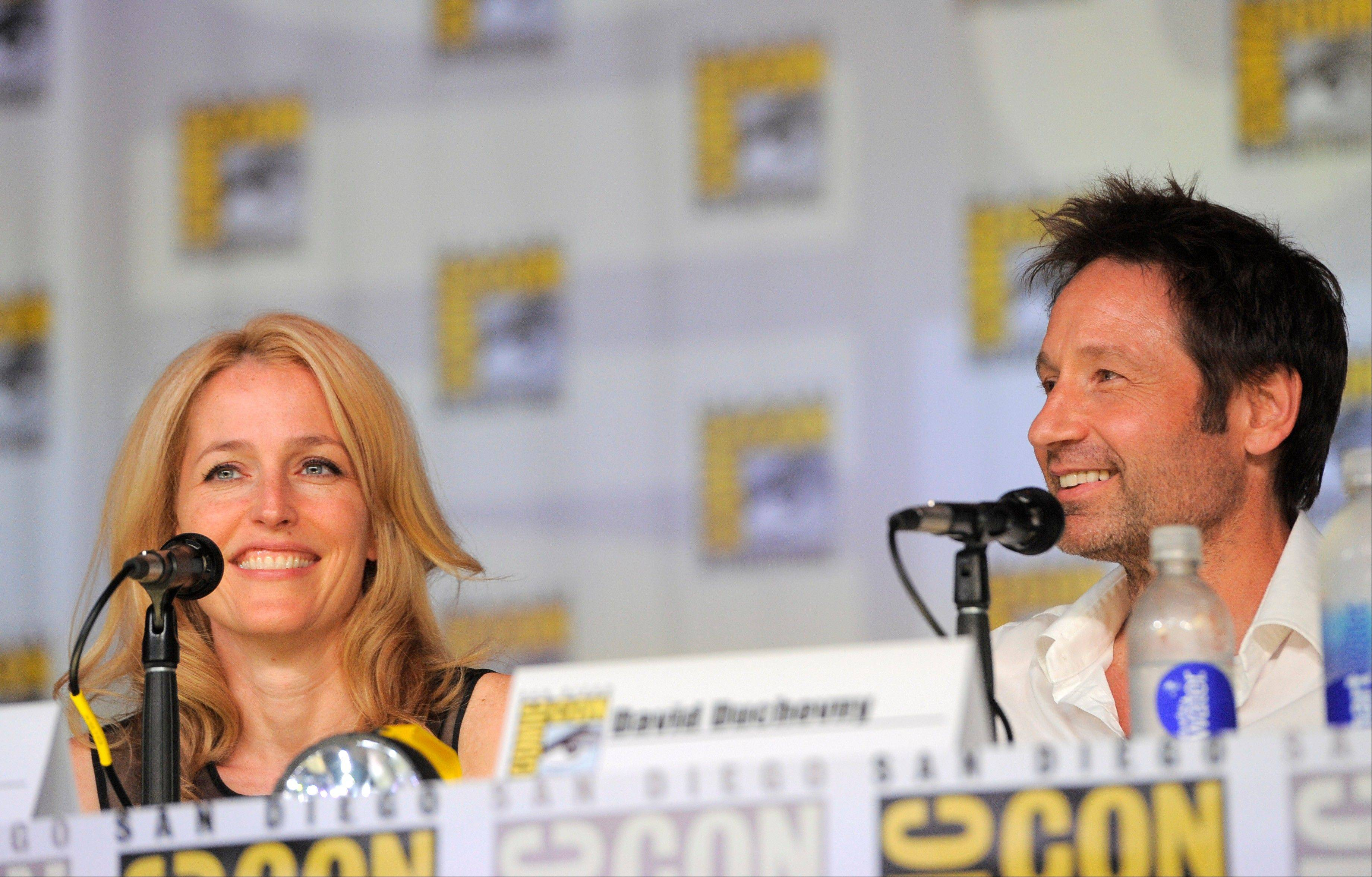 "Gillian Anderson, left, and David Duchovny attend the ""The X-Files"" 20th Anniversary panel Thursday at Comic-Con International in San Diego."