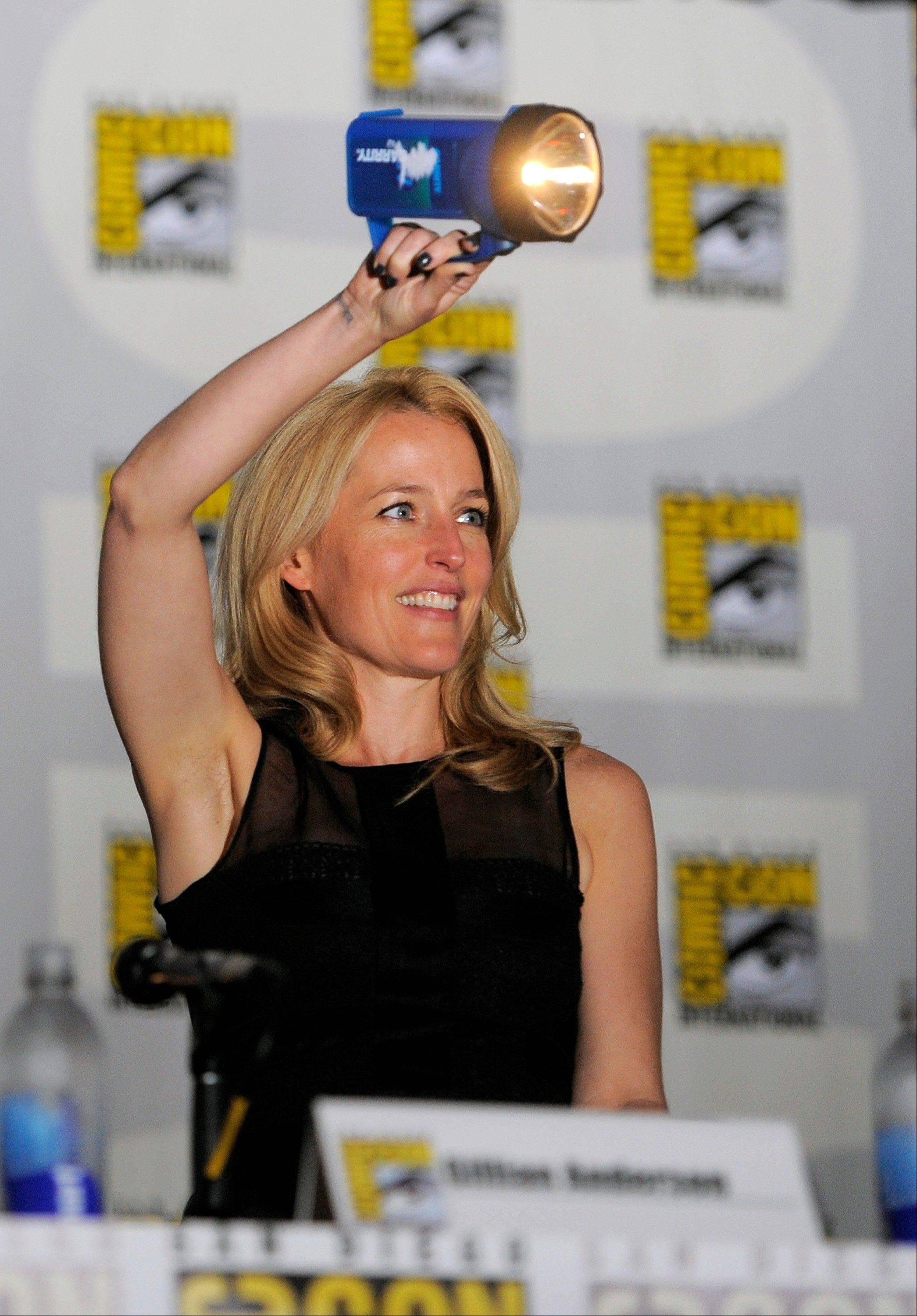 "Gillian Anderson shines a flashlight on fans at the ""The X-Files"" 20th Anniversary panel Thursday at Comic-Con International in San Diego."