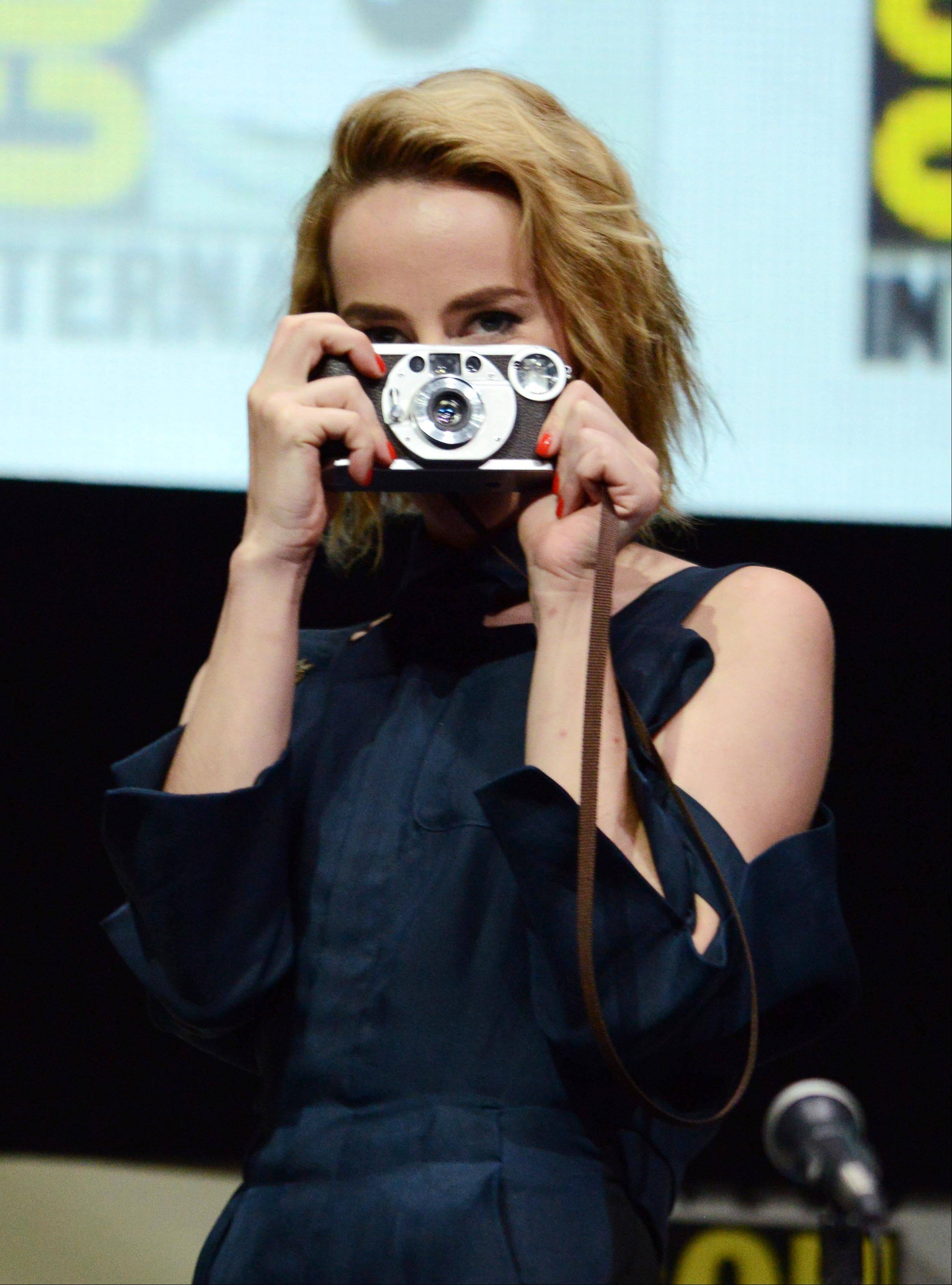 "Jena Malone, who plays Johanna Mason, takes a picture of fans in Hall H at the ""The Hunger Games: Catching Fire"" panel Saturday during Day 4 of Comic-Con International in San Diego. ""Catching Fire"" opens Nov. 22 in theaters."