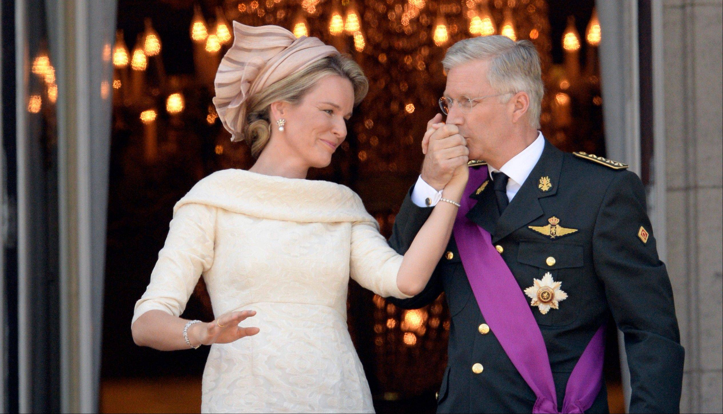 Belgium's King Philippe, right, kisses the hand of Queen Mathilde as they stand on the balcony of the royal palace in Brussels on Sunday, July 21, 2013. Philippe has taken the oath before parliament to become Belgium's seventh king after his father Albert II abdicated as the head of this fractured nation. Earlier Sunday, the 79-year-old Albert signed away his rights as the kingdom's largely ceremonial ruler at the royal palace in the presence of Prime Minister Elio Di Rupo, who holds the political power in this 183-year-old parliamentary democracy.