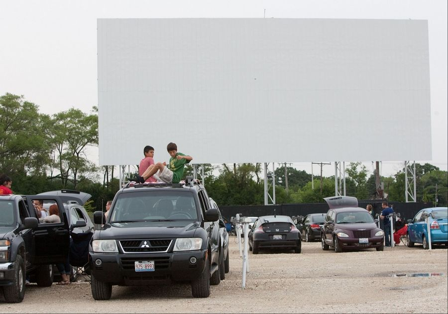 Patrons prepare to watch a movie -- projected by a new digital system -- at the Cascade Drive-In in West Chicago.