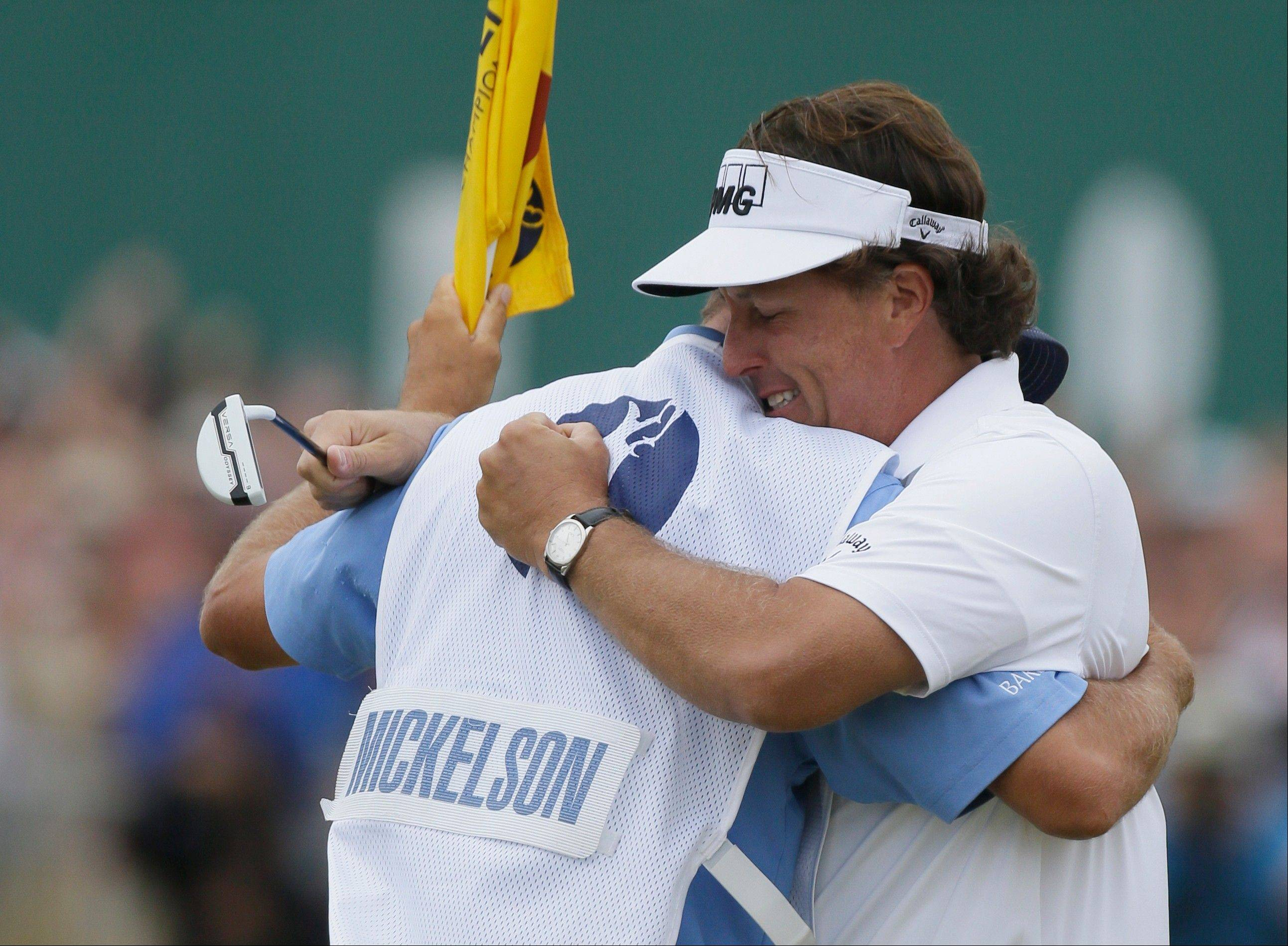 Phil Mickelson celebrates after his final putt on the 18th green with his caddie Jim Mackay during the final round Sunday of the British Open Golf Championship at Muirfield, Scotland.