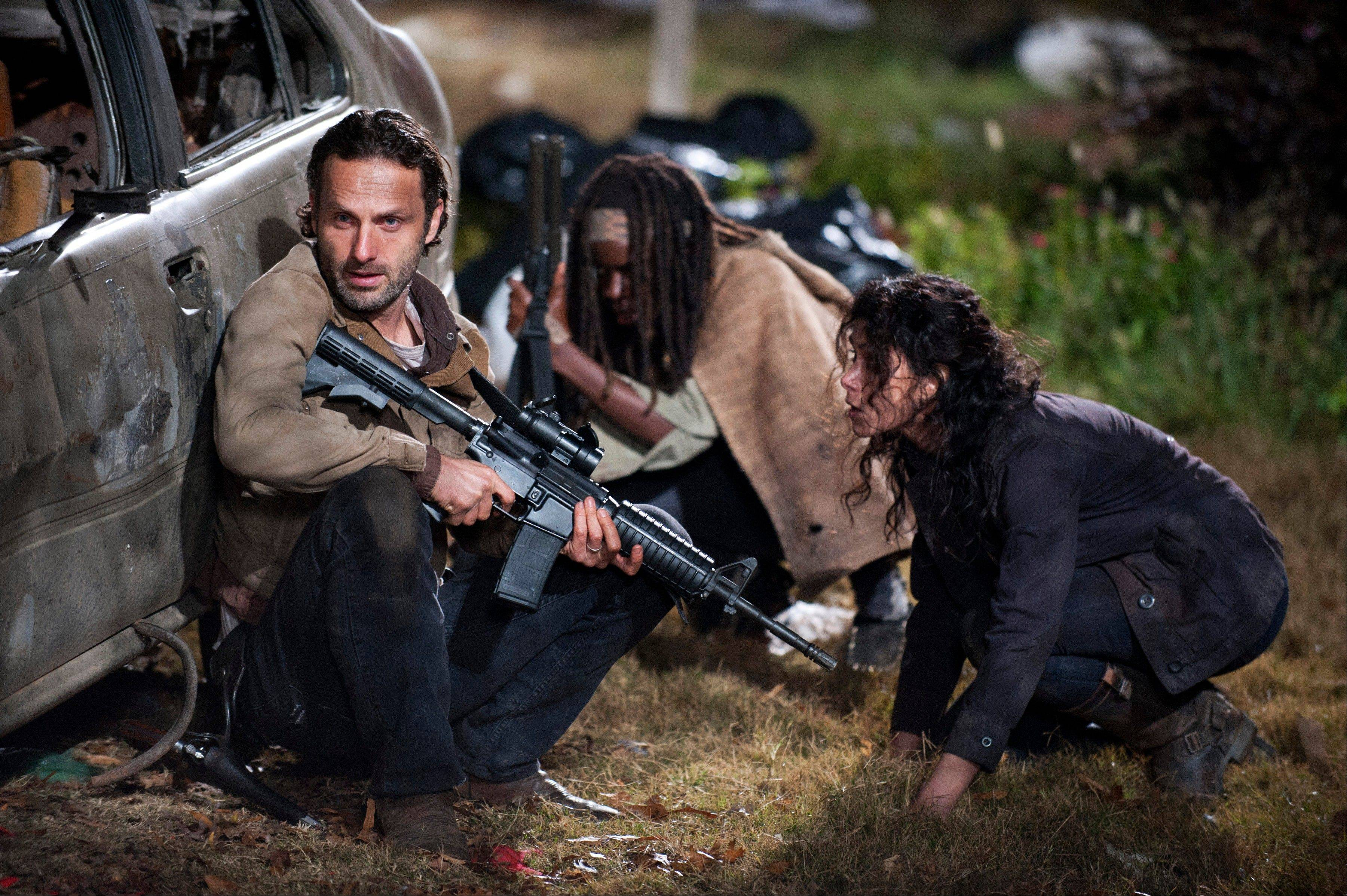 "AMC's ""The Walking Dead"" got a boost from being promoted at Comic-Con. Andrew Lincoln, left, as Rick Grimes, Danai Gurira as Michonne and Melissa Ponzio as Karen in a scene from Episode 16, ""Welcome to the Tombs,"" from Season 3 of the series."