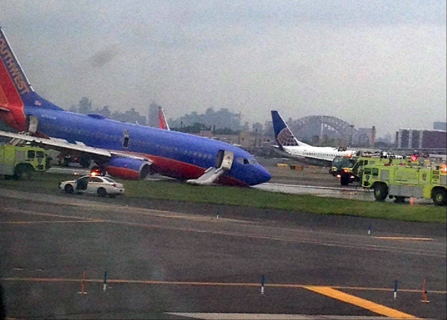 ASSOCIATED PRESS/Jared Rosenstein A Southwest Airlines plane whose nose gear collapsed as it touched down on the runway is surrounded by emergency vehicles at LaGuardia Airport in New York on Monday. The plane was carrying 149 passengers and crew.