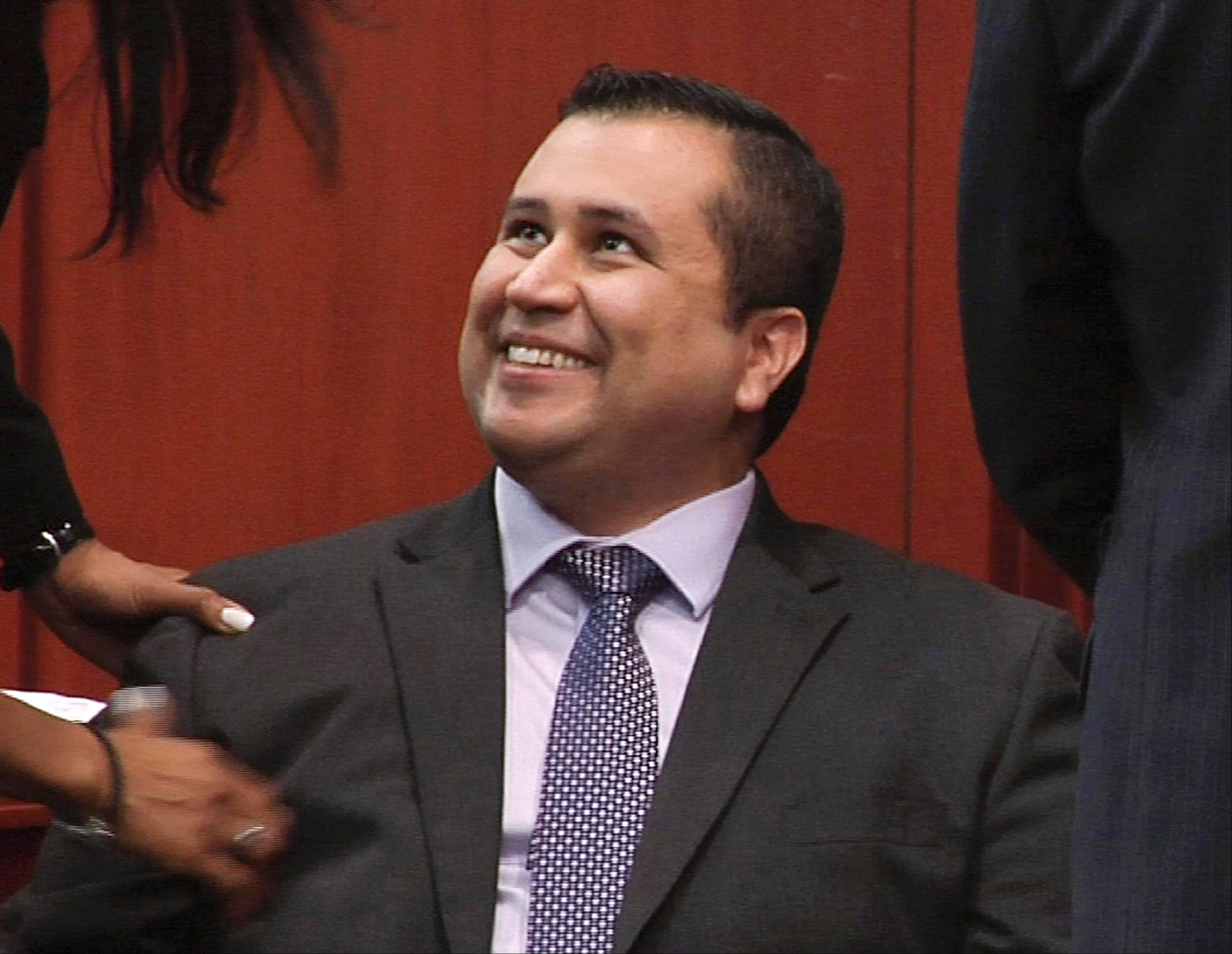 In this file image from video, George Zimmerman smiles after a not guilty verdict was handed down in his trial at the Seminole County Courthouse, Sunday, July 14, 2013, in Sanford, Fla. Officials say Zimmerman helped rescue four people from an overturned vehicle last week, just days after he was cleared of all charges in the shooting death of Trayvon Martin.