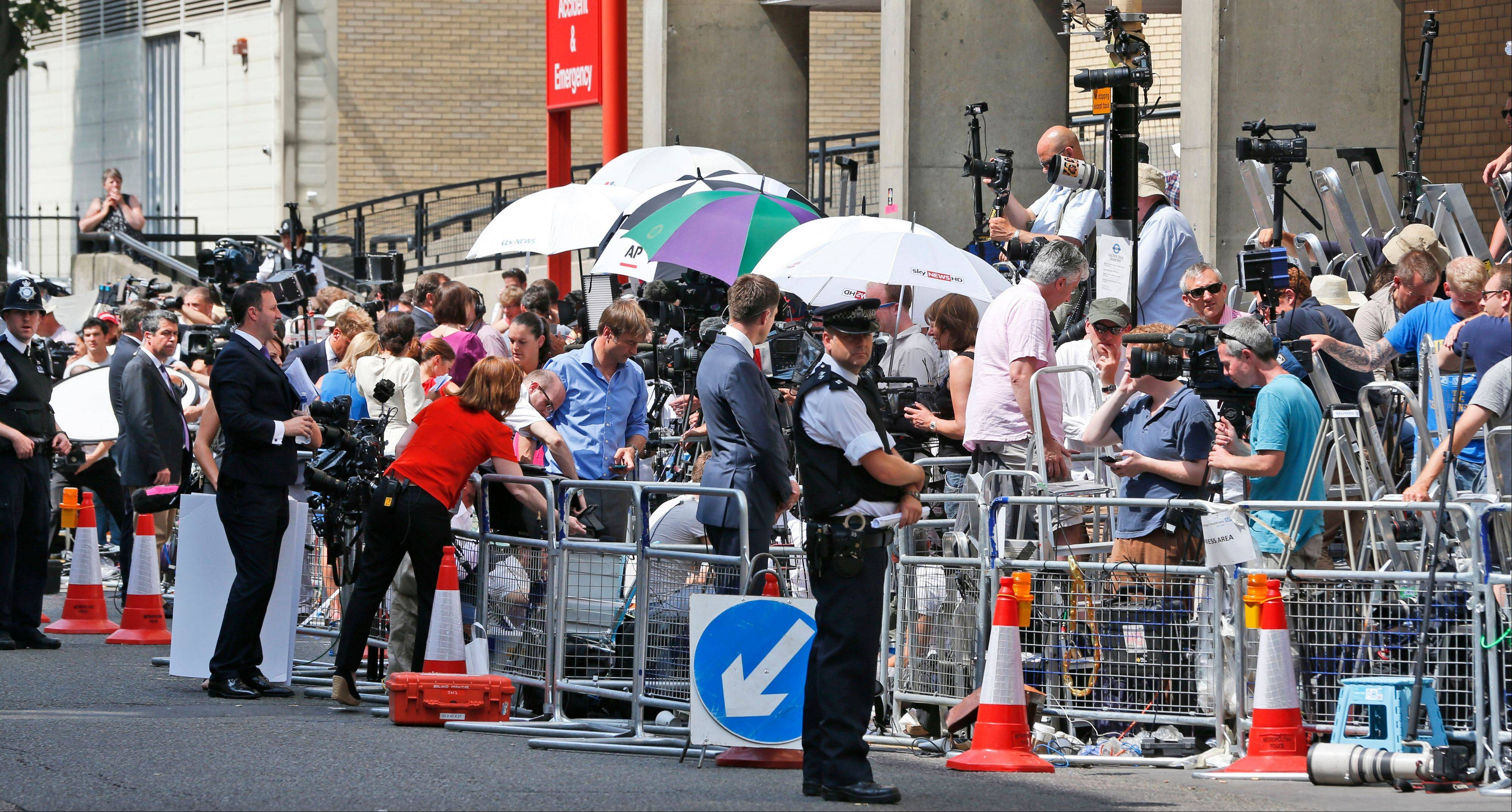 A British police officer, backdropped by members of the media, stands outside St. Mary�s Hospital exclusive Lindo Wing in London, Monday.