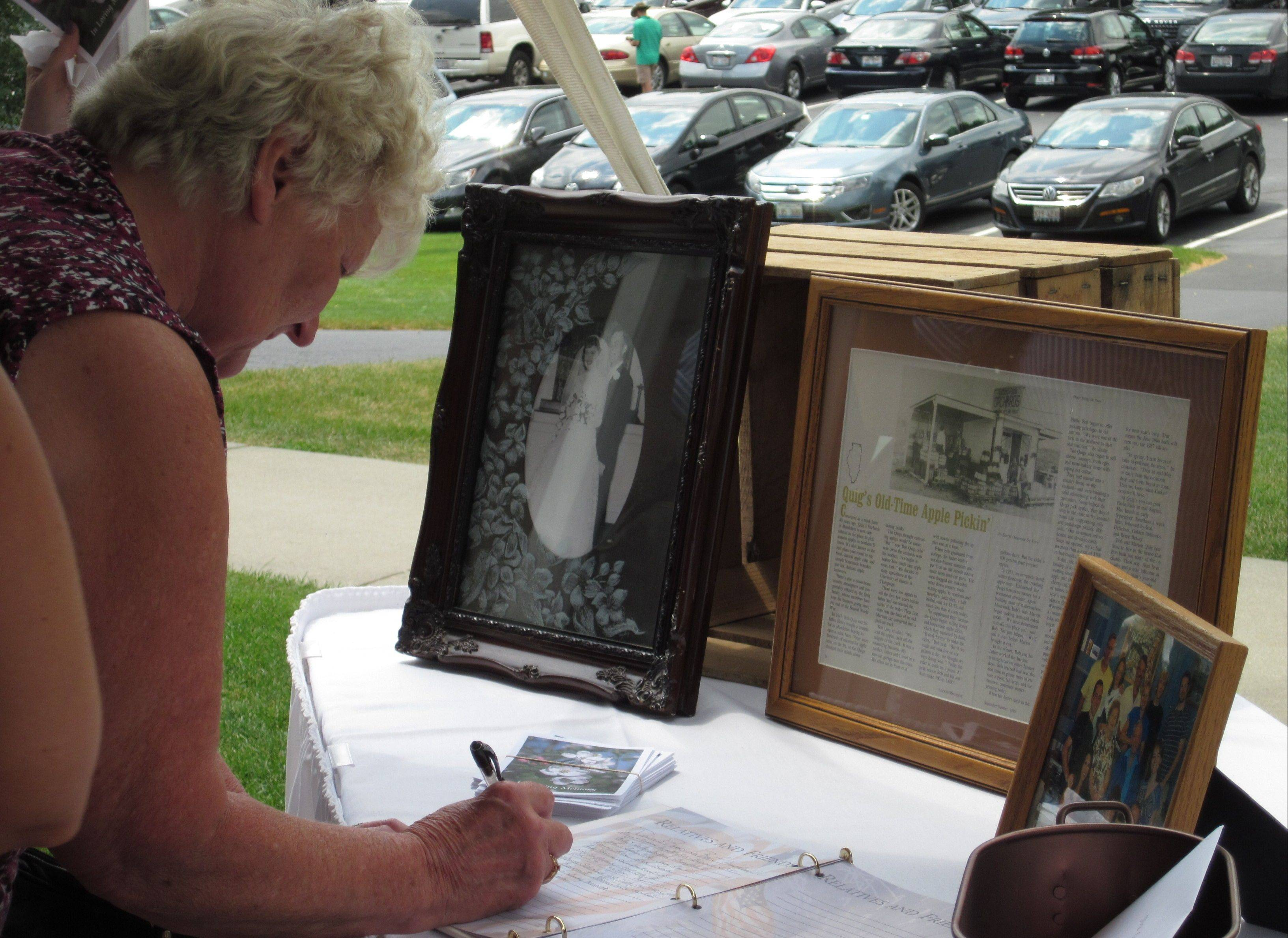 Cheryl Roels, of Mundelein, signs the guest book during a memorial service Sunday for former apple orchard owner Bob Quig.